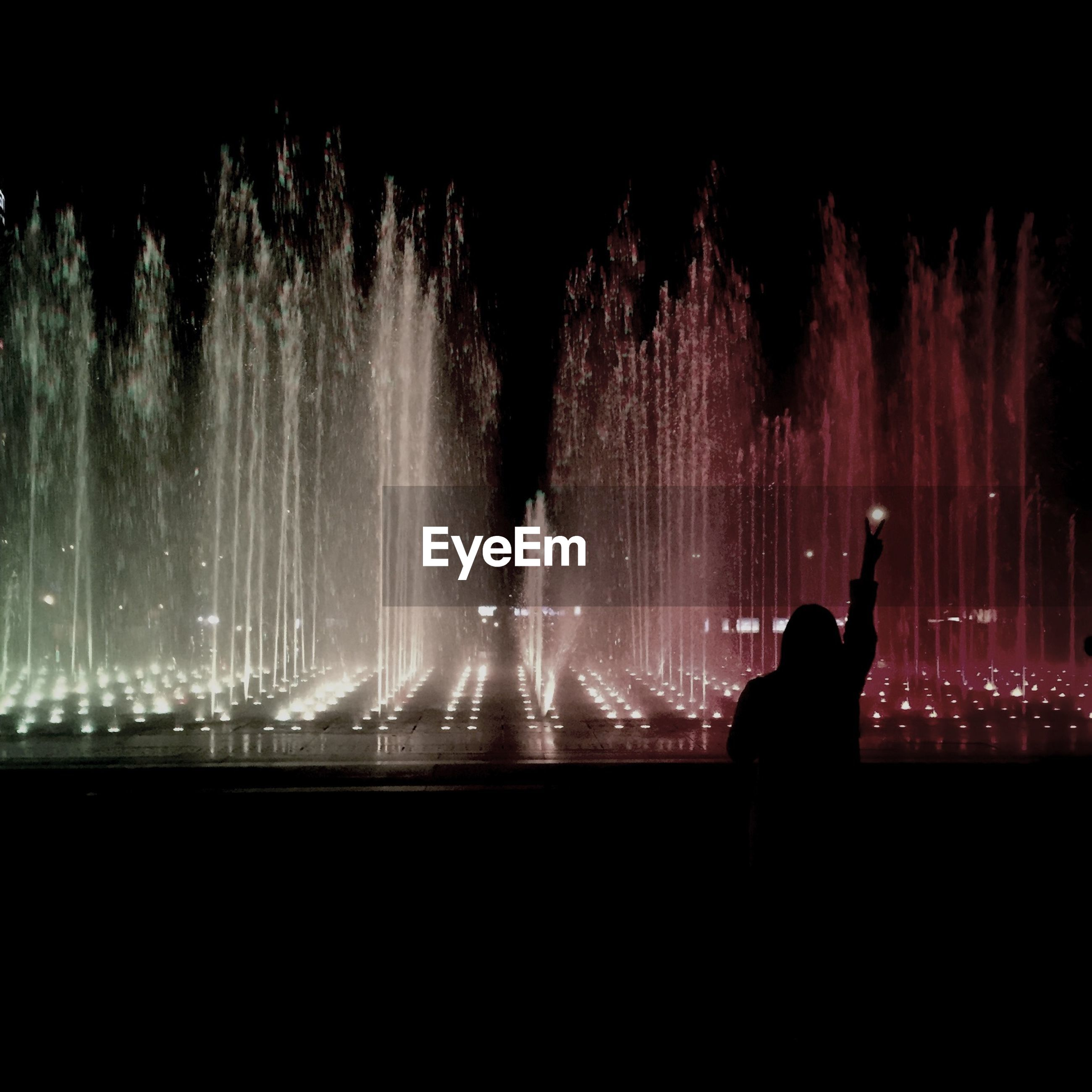 night, illuminated, silhouette, men, lifestyles, dark, leisure activity, long exposure, motion, unrecognizable person, person, arts culture and entertainment, glowing, light, standing, fountain, light - natural phenomenon, rear view, event