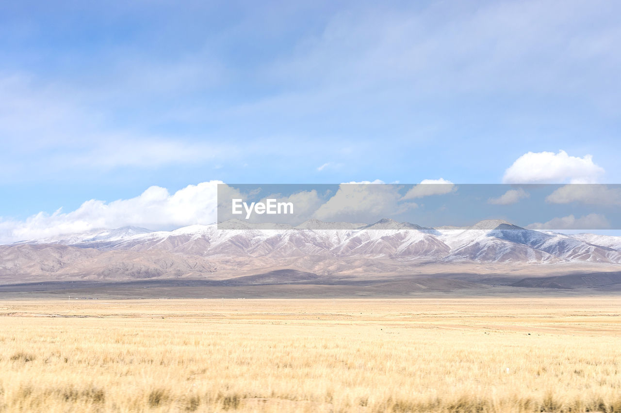 scenics - nature, sky, tranquil scene, mountain, environment, beauty in nature, tranquility, landscape, cloud - sky, non-urban scene, day, no people, mountain range, nature, idyllic, grass, land, cold temperature, winter, snow, snowcapped mountain, outdoors, arid climate