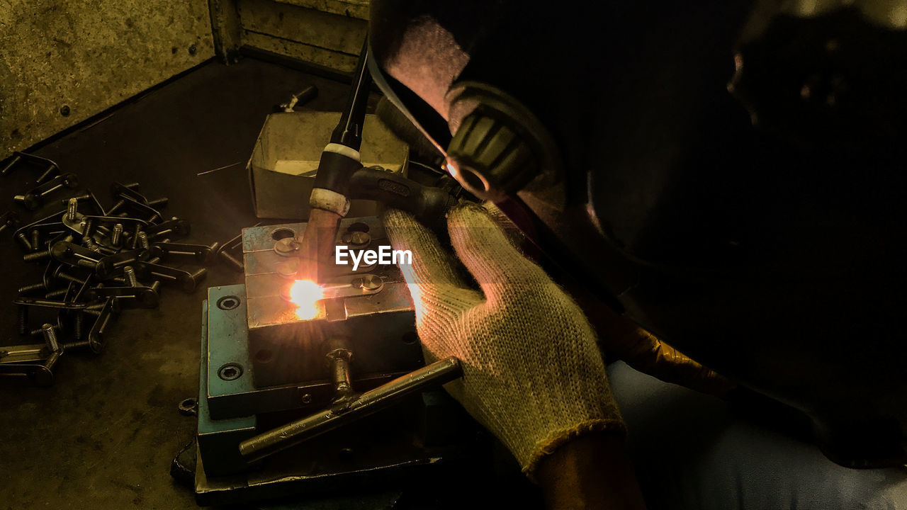 High Angle View Worker Welding Wood With Equipment