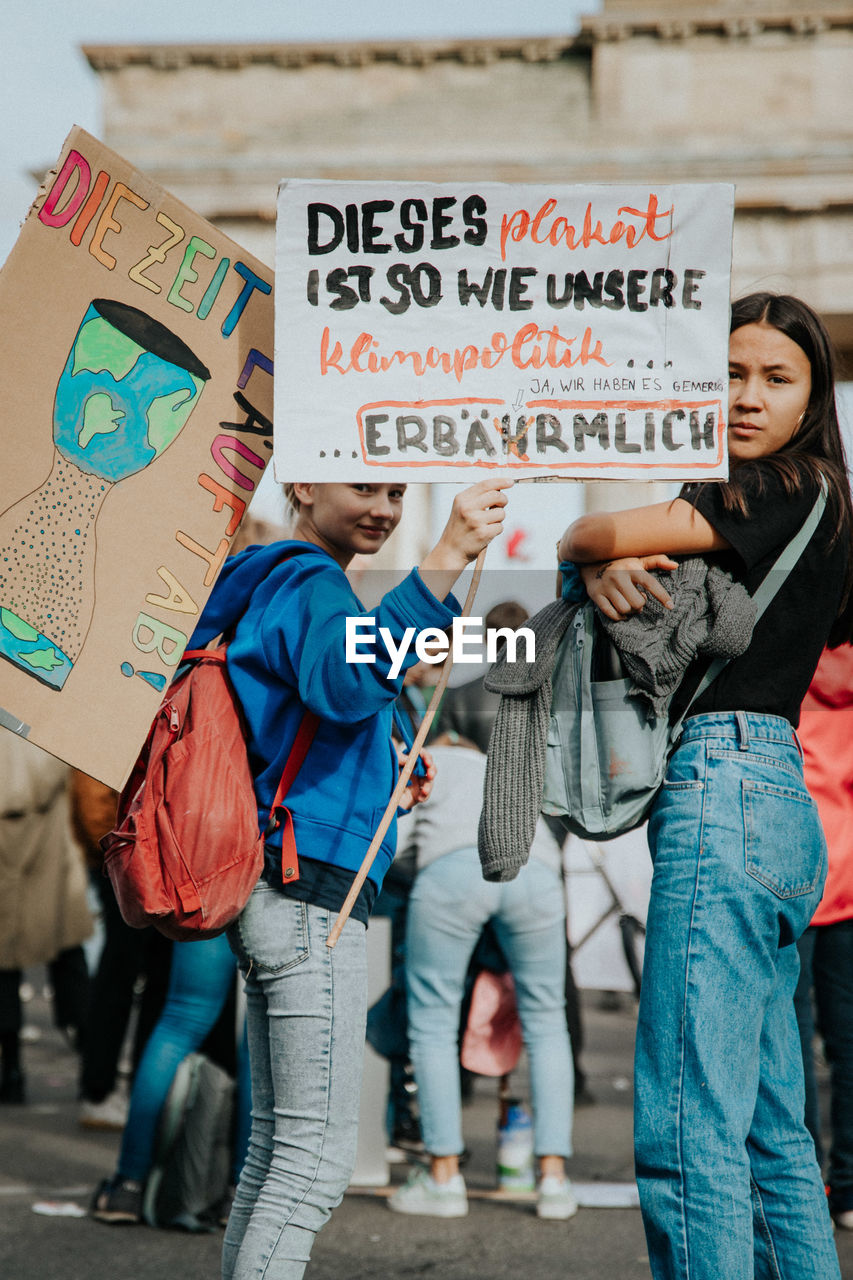 text, communication, group of people, real people, western script, holding, medium group of people, sign, casual clothing, architecture, women, group, three quarter length, placard, day, script, information, protest, young adult, people, protestor, message