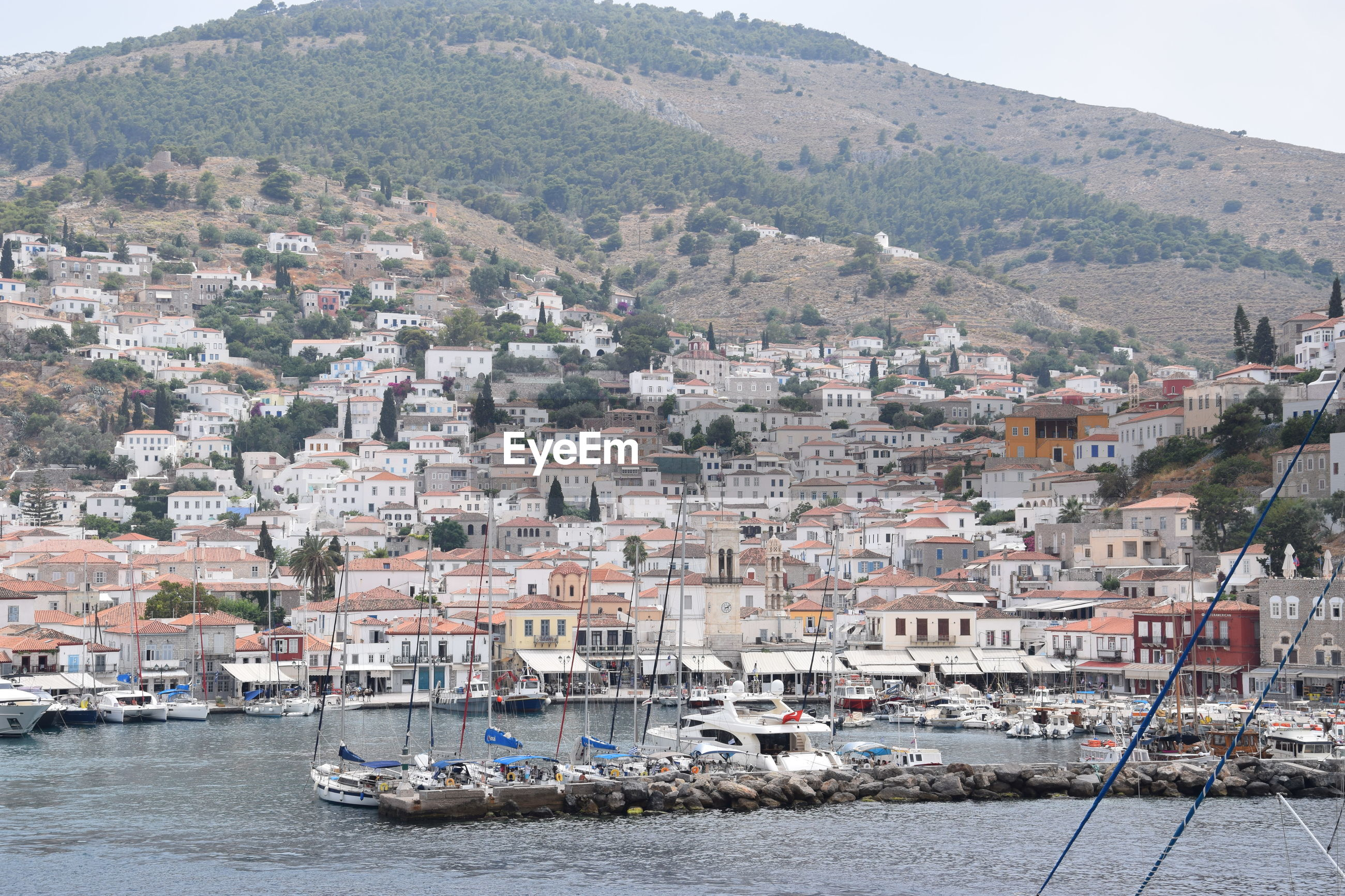 HIGH ANGLE VIEW OF TOWNSCAPE BY SEA AGAINST MOUNTAIN