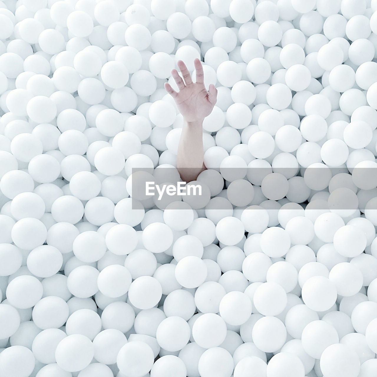 Cropped Image Of Hand Emitting From White Ball Pool