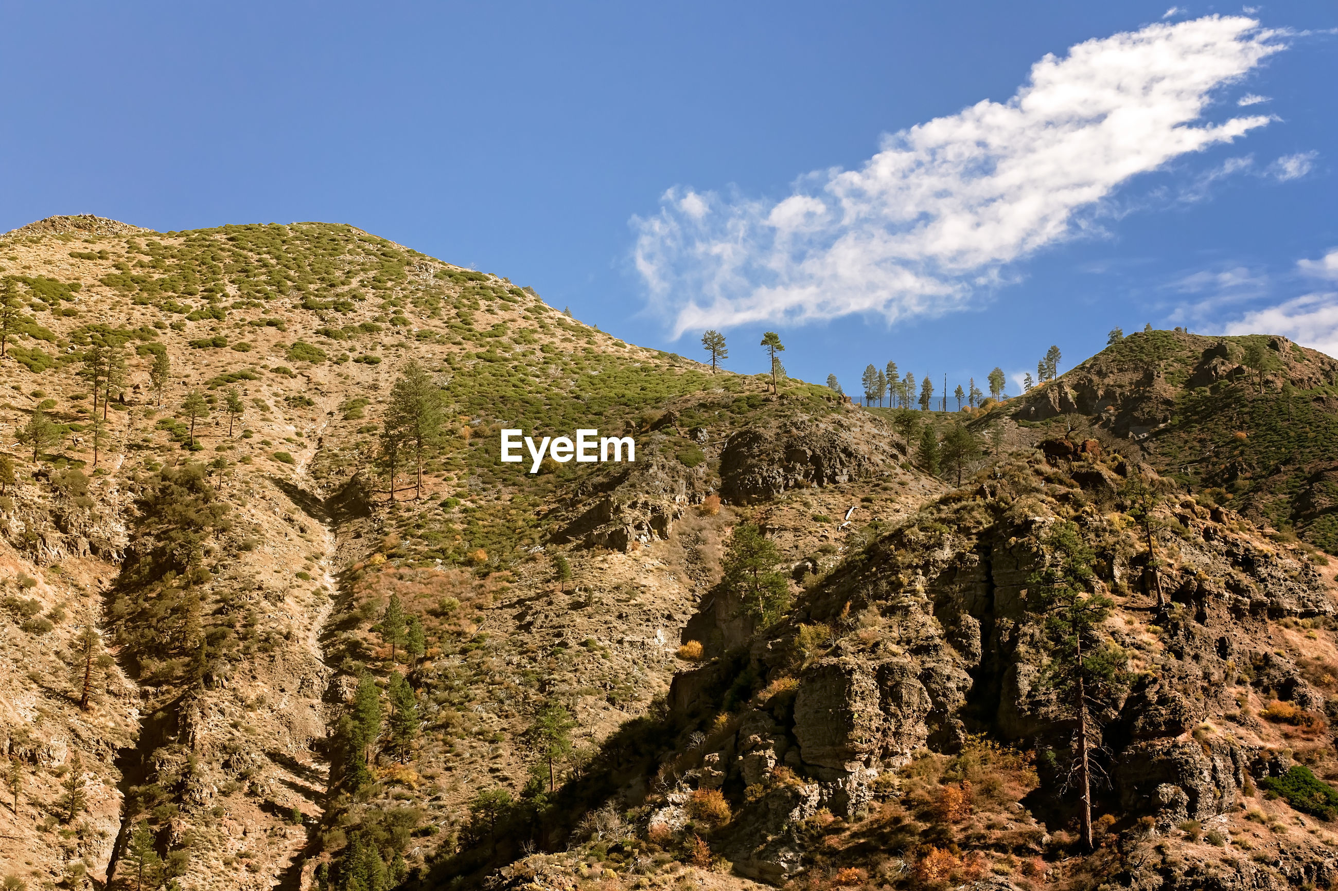 LOW ANGLE VIEW OF ROCKS ON MOUNTAIN AGAINST SKY