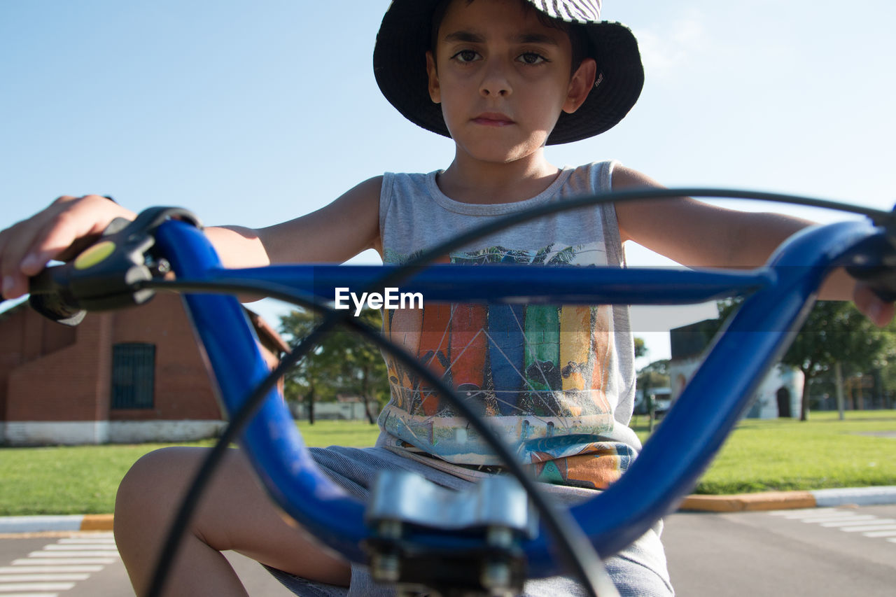 Low angle portrait of boy riding bicycle on road against sky