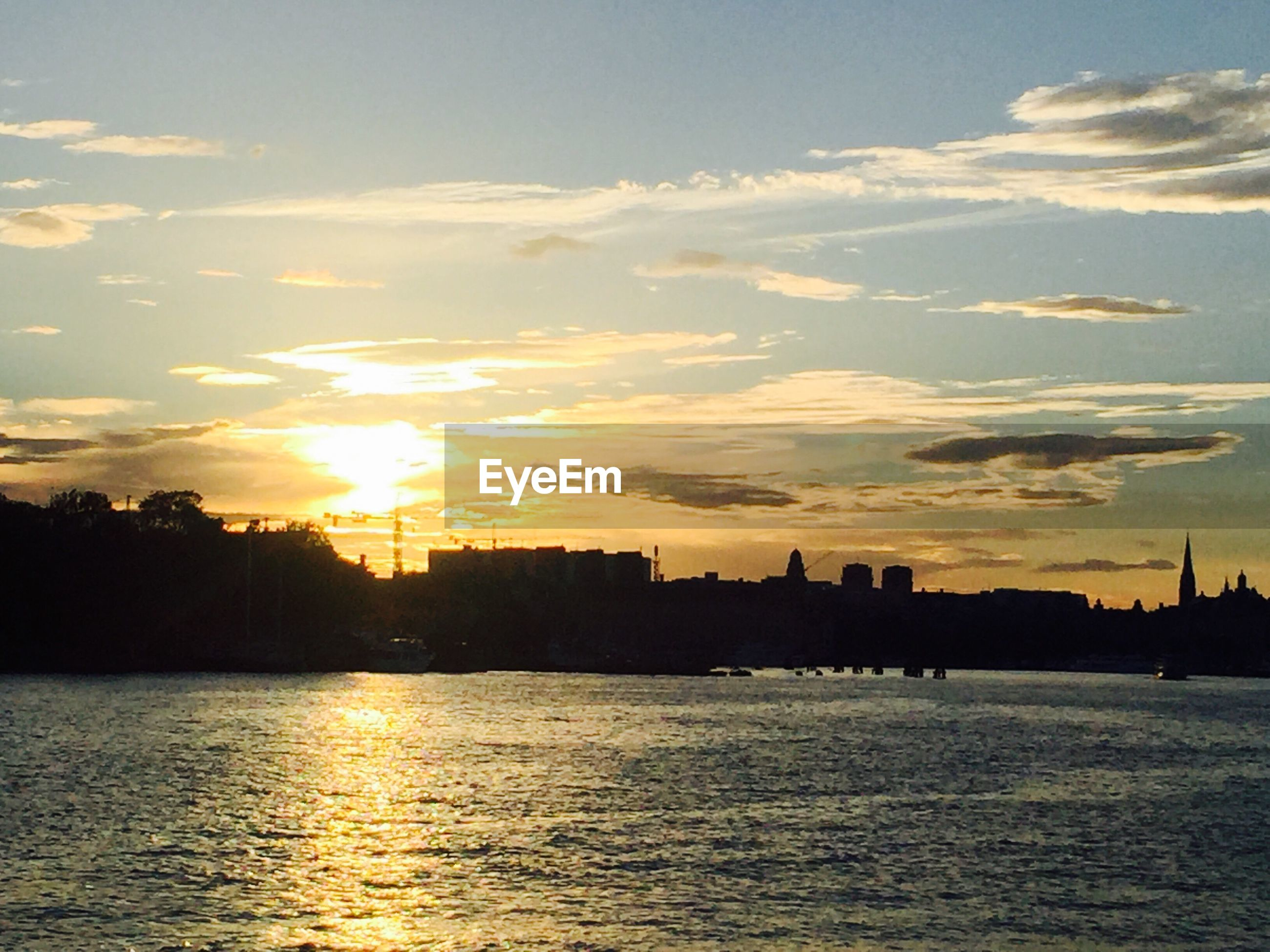 sunset, architecture, building exterior, water, built structure, city, waterfront, silhouette, river, sky, scenics, cityscape, cloud - sky, sun, cloud, skyline, urban skyline, calm, sea, beauty in nature, outdoors, nature, tranquility, tranquil scene, distant, no people, residential district, riverbank
