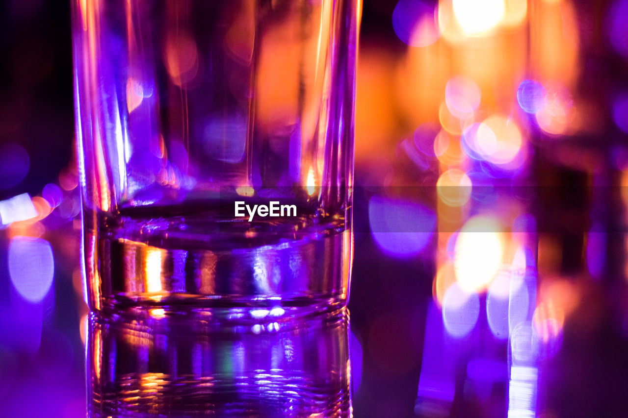 close-up, illuminated, indoors, food and drink, glass - material, no people, focus on foreground, night, household equipment, glass, transparent, pink color, drink, refreshment, purple, still life, drinking glass, reflection, nightlife
