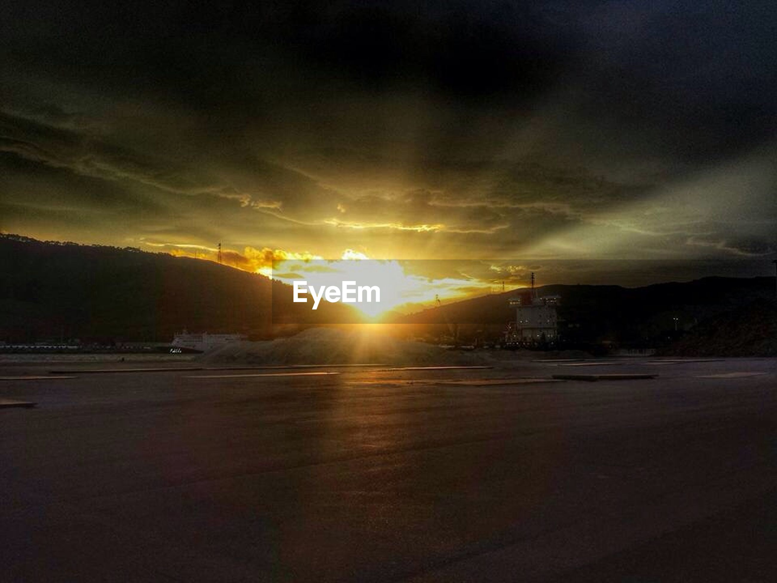 sunset, mountain, sun, building exterior, sky, cloud, architecture, cloud - sky, sunbeam, tranquil scene, water, scenics, tranquility, beauty in nature, outdoors, nature, mountain range, dramatic sky, lens flare, storm cloud, majestic, cloudy