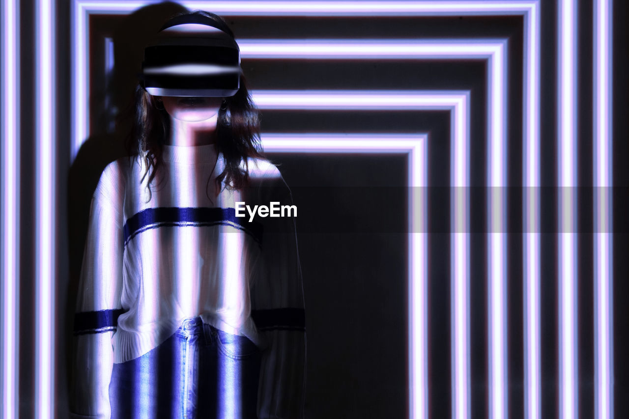 Young woman wearing virtual reality simulator standing against illuminated background