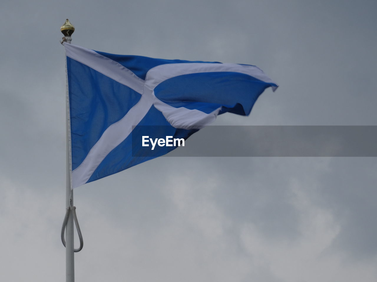 Low Angle View Of Scottish Flag Against Cloudy Sky