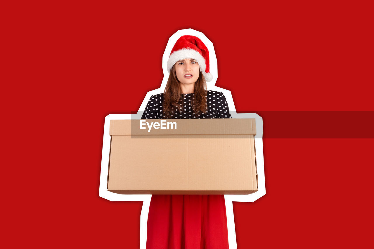 Portrait of young woman holding cardboard box against red background