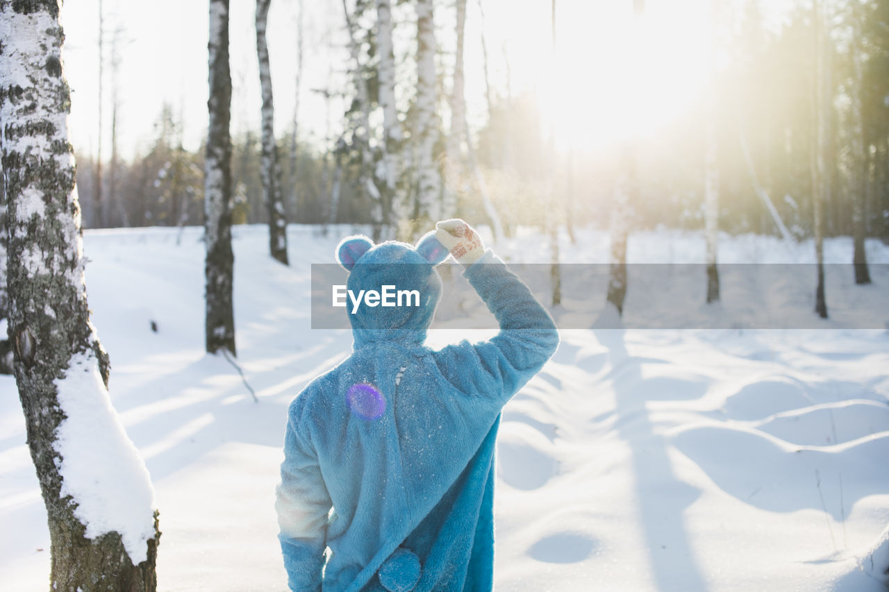 Rear View Of Mid Adult Man Standing On Snow Covered Field In Forest