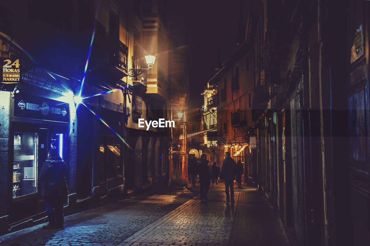 night, architecture, illuminated, building exterior, built structure, city, real people, street, walking, direction, city life, the way forward, men, building, rear view, lifestyles, people, residential district, group of people, transportation, outdoors, nightlife