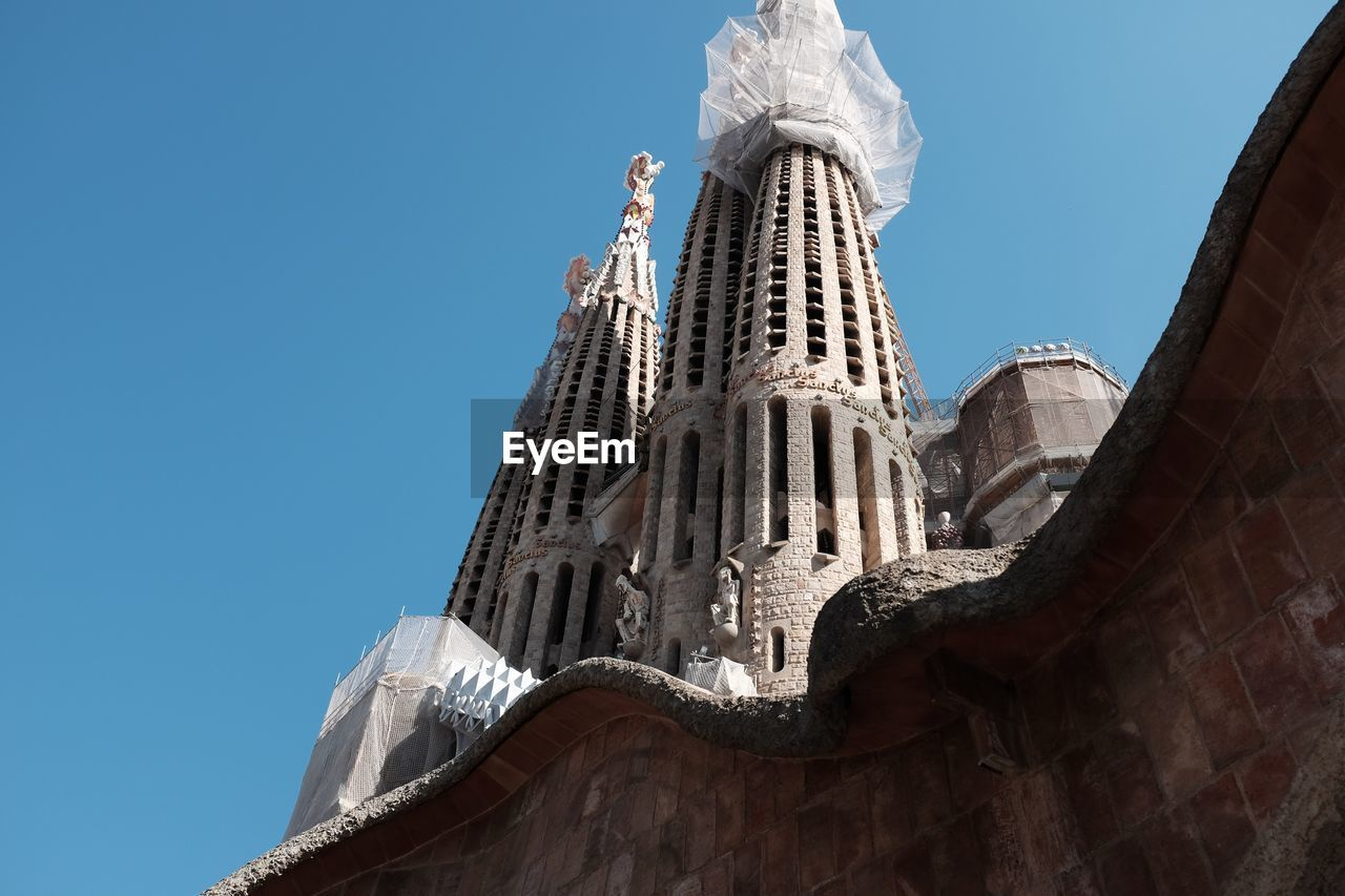 Low Angle View Of Sagrada Familia With Scaffolding Against Clear Sky