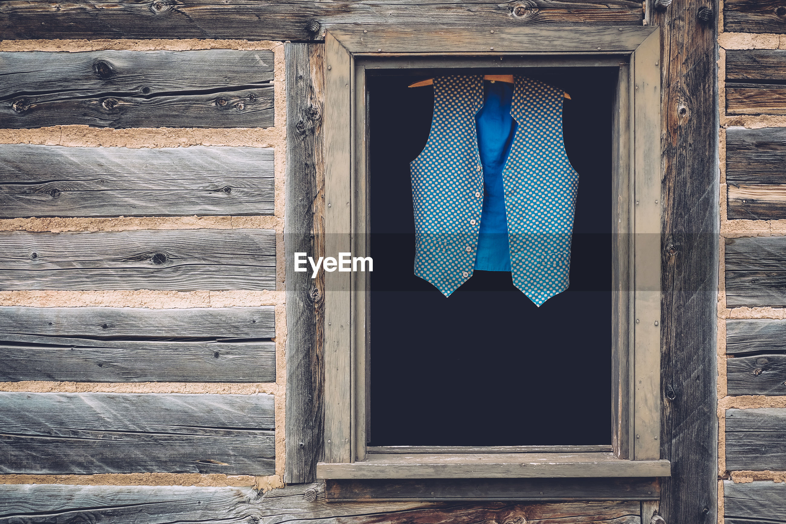 Blue waistcoat hanging on coathanger at window in log cabin