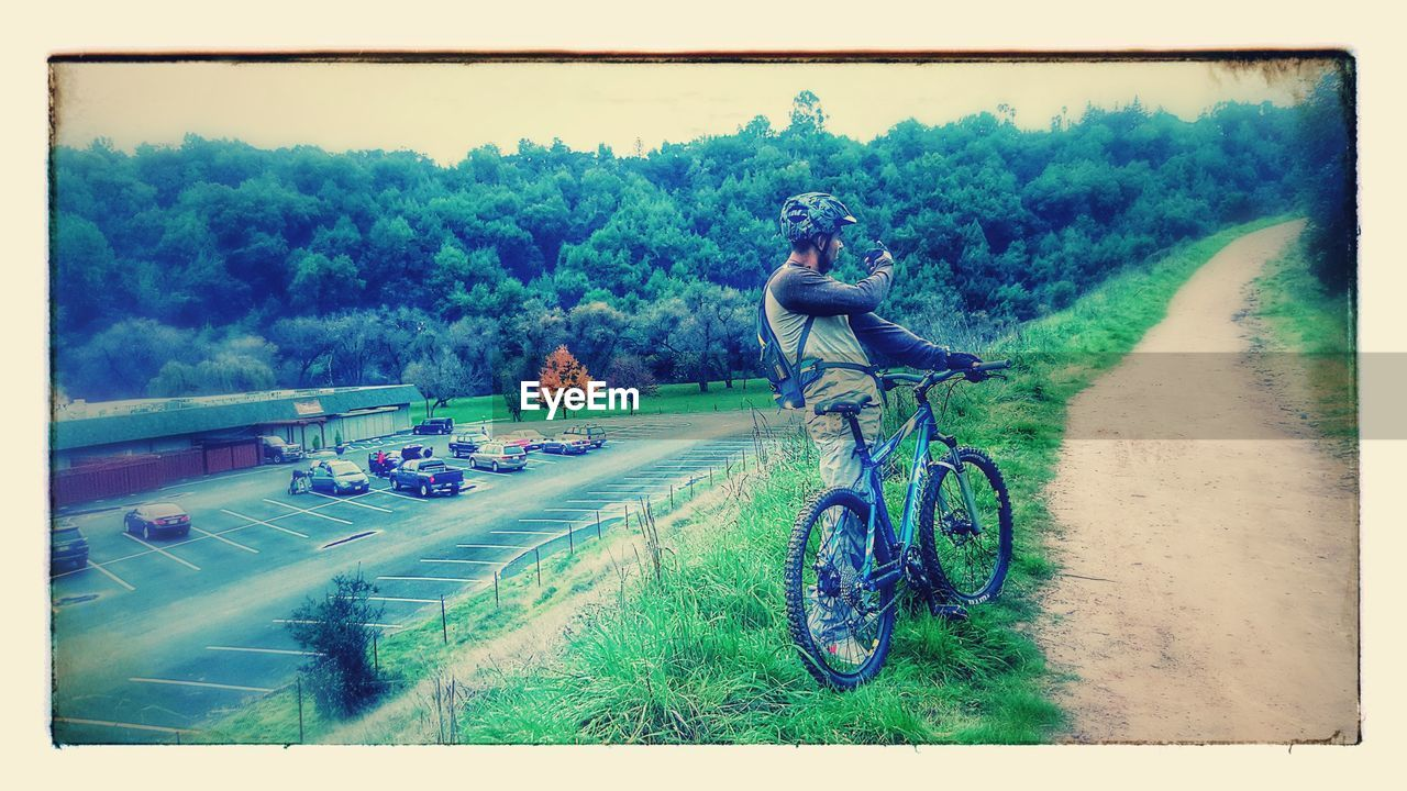 bicycle, transportation, tree, day, full length, real people, field, grass, outdoors, nature, mode of transport, leisure activity, land vehicle, landscape, men, two people, adventure, sky, young adult, young women, people