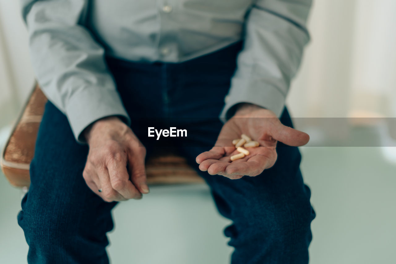 Midsection of senior man sitting on chair holding medicine pills in palm - fucus on fingers