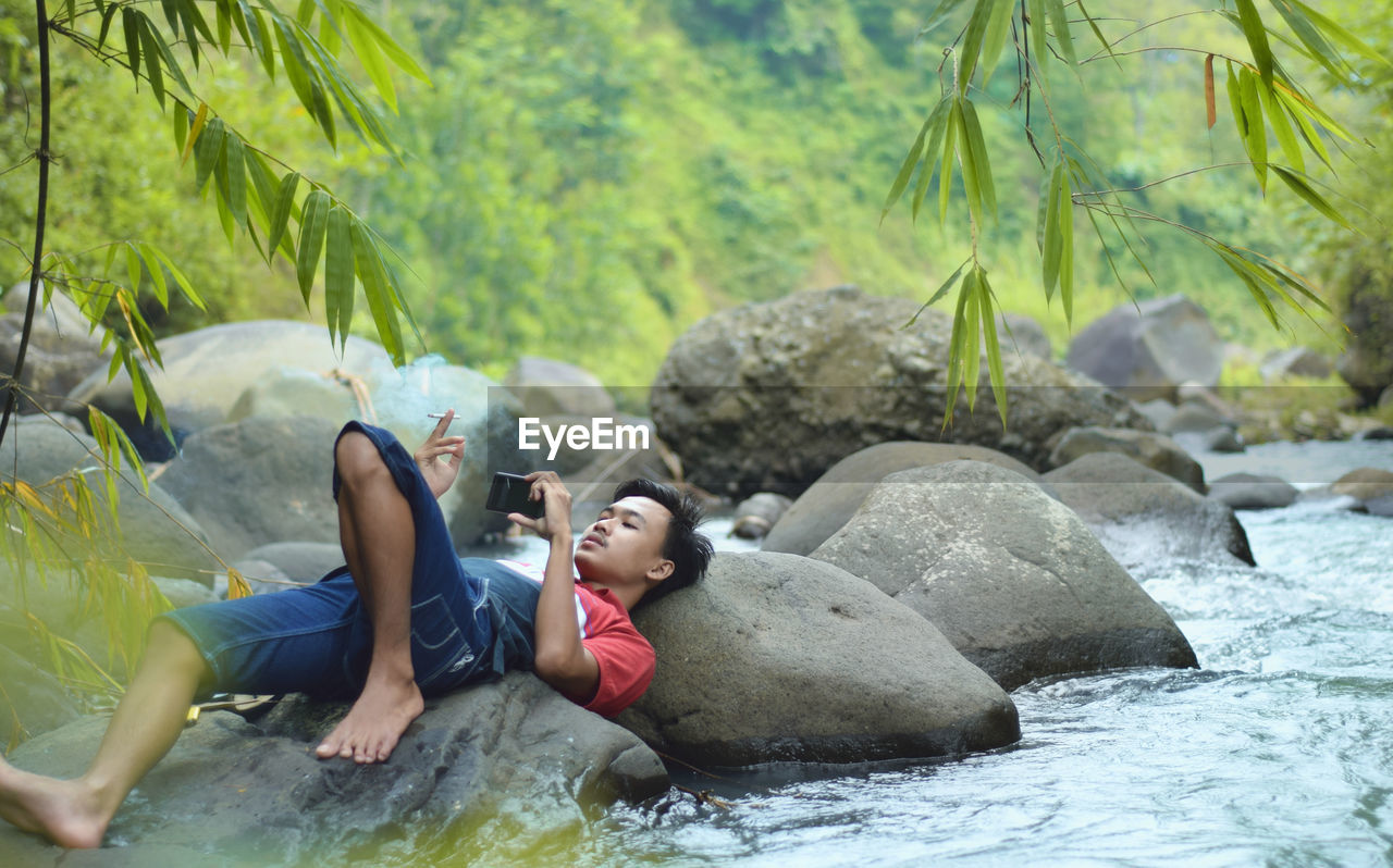 Full Length Of Man Relaxing On Rock While Using Smart Phone By River