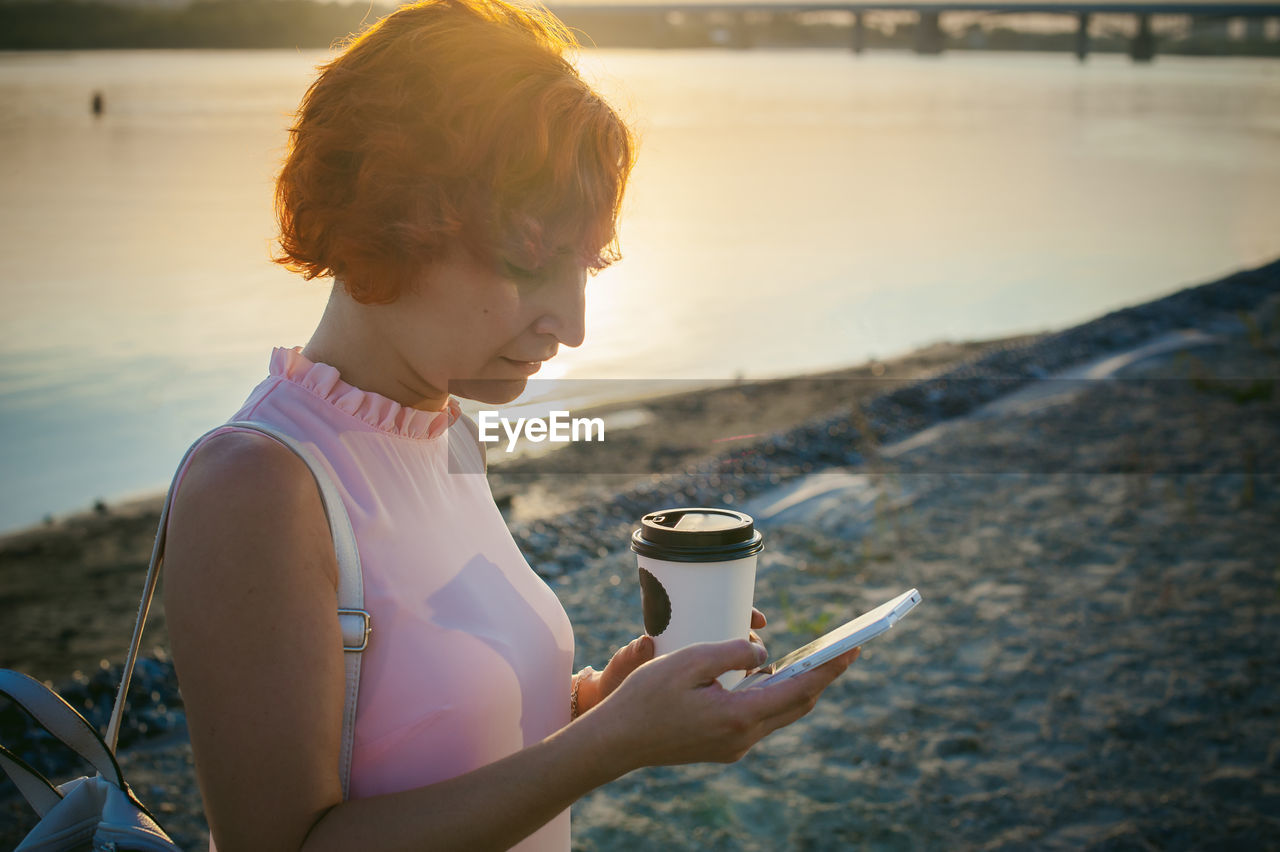 Mid adult woman using mobile phone while standing by river against sky during sunset