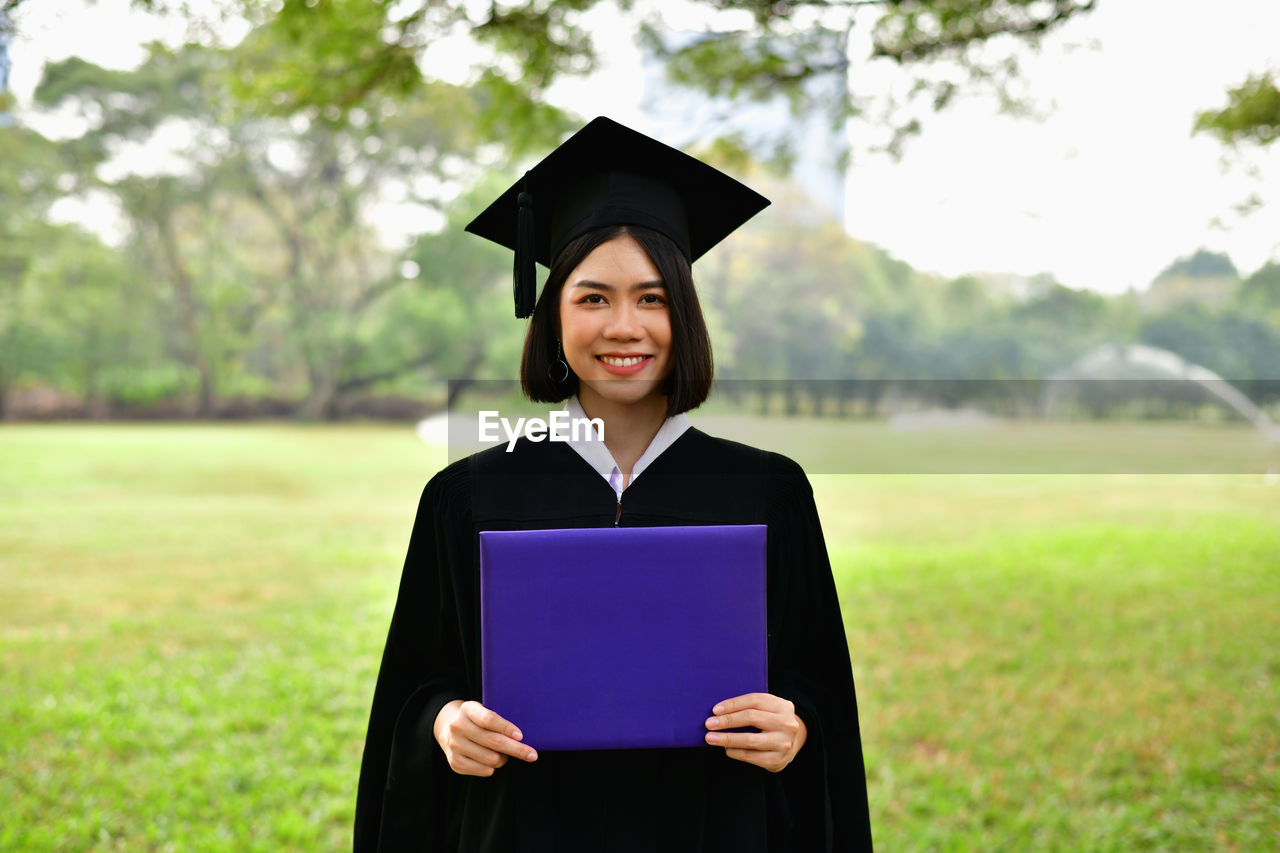 graduation, education, one person, university, graduation gown, student, grass, mortarboard, young adult, university student, achievement, standing, smiling, portrait, focus on foreground, field, plant, real people, learning, outdoors, teenager