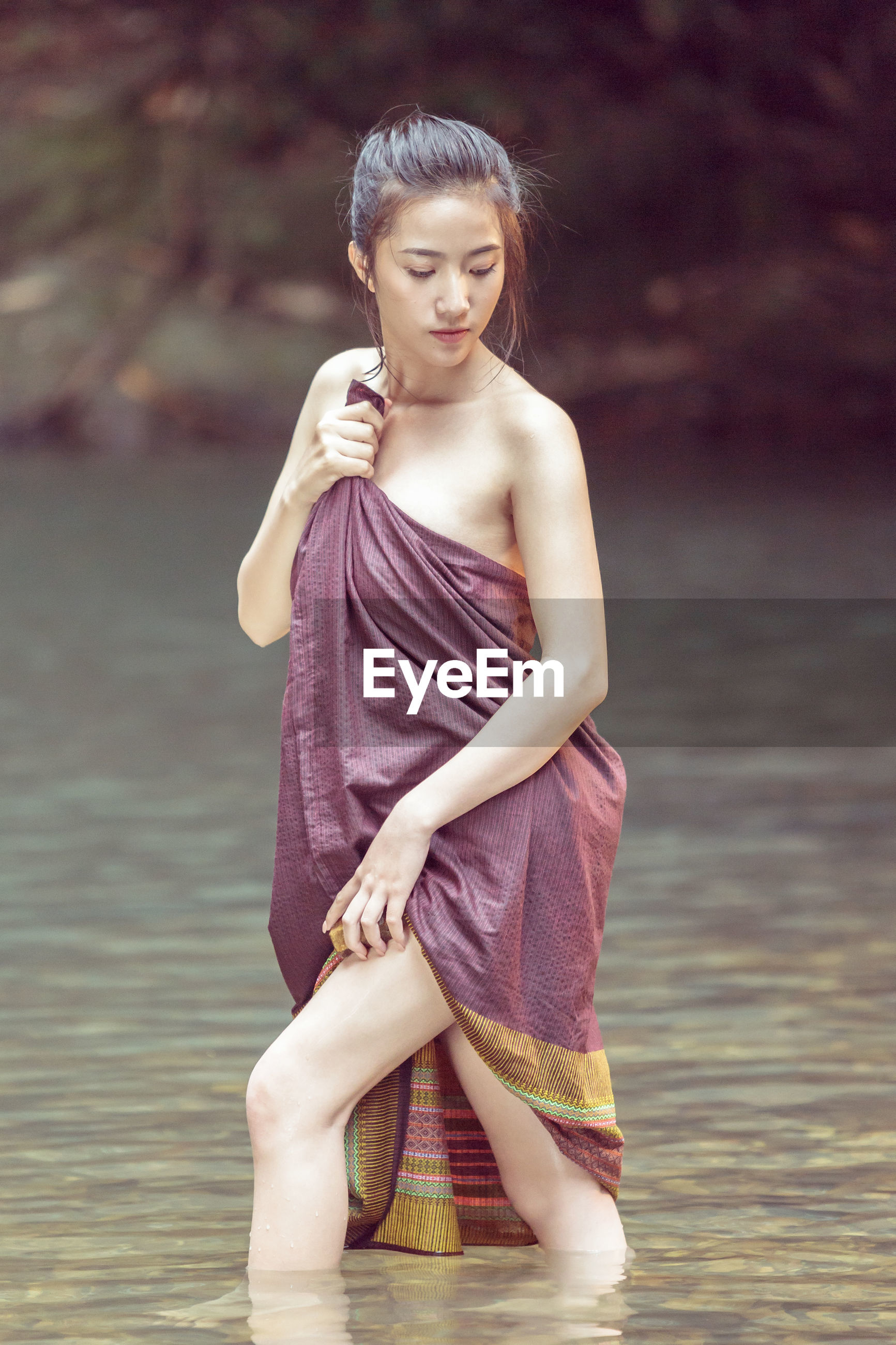 Woman wrapped in fabric standing in river