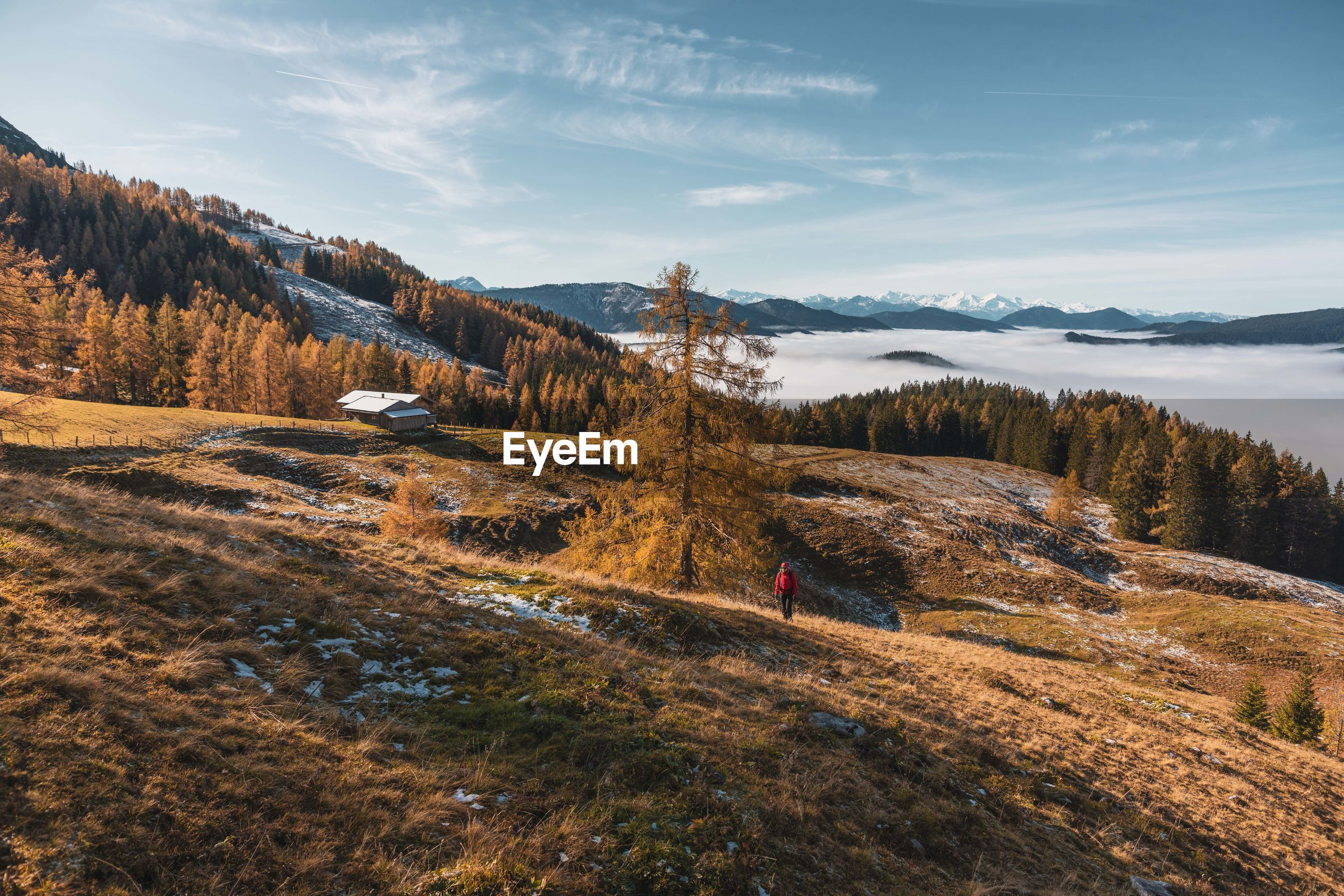 High angle view of woman hiking on mountain against sky during winter