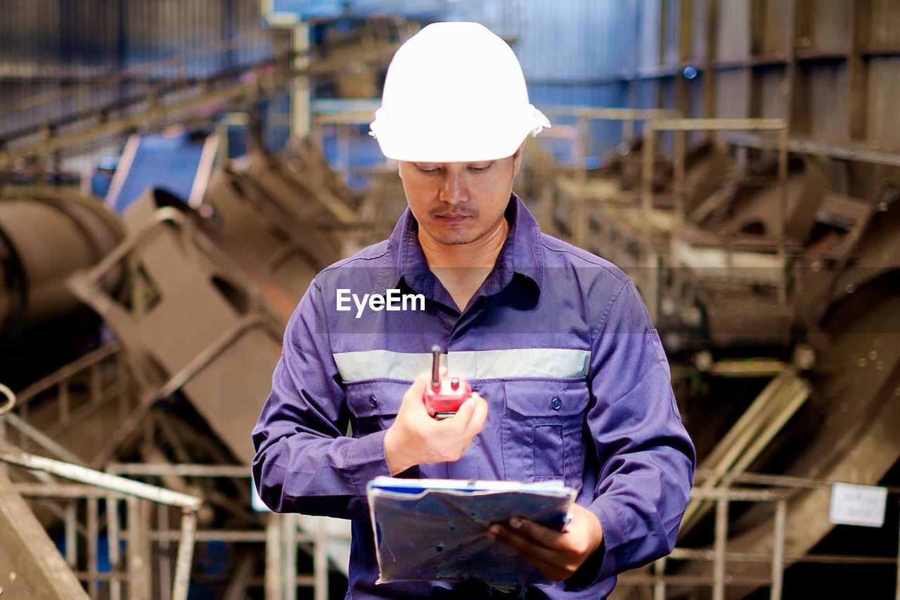 Engineer looking at walkie-talkie while standing in workshop