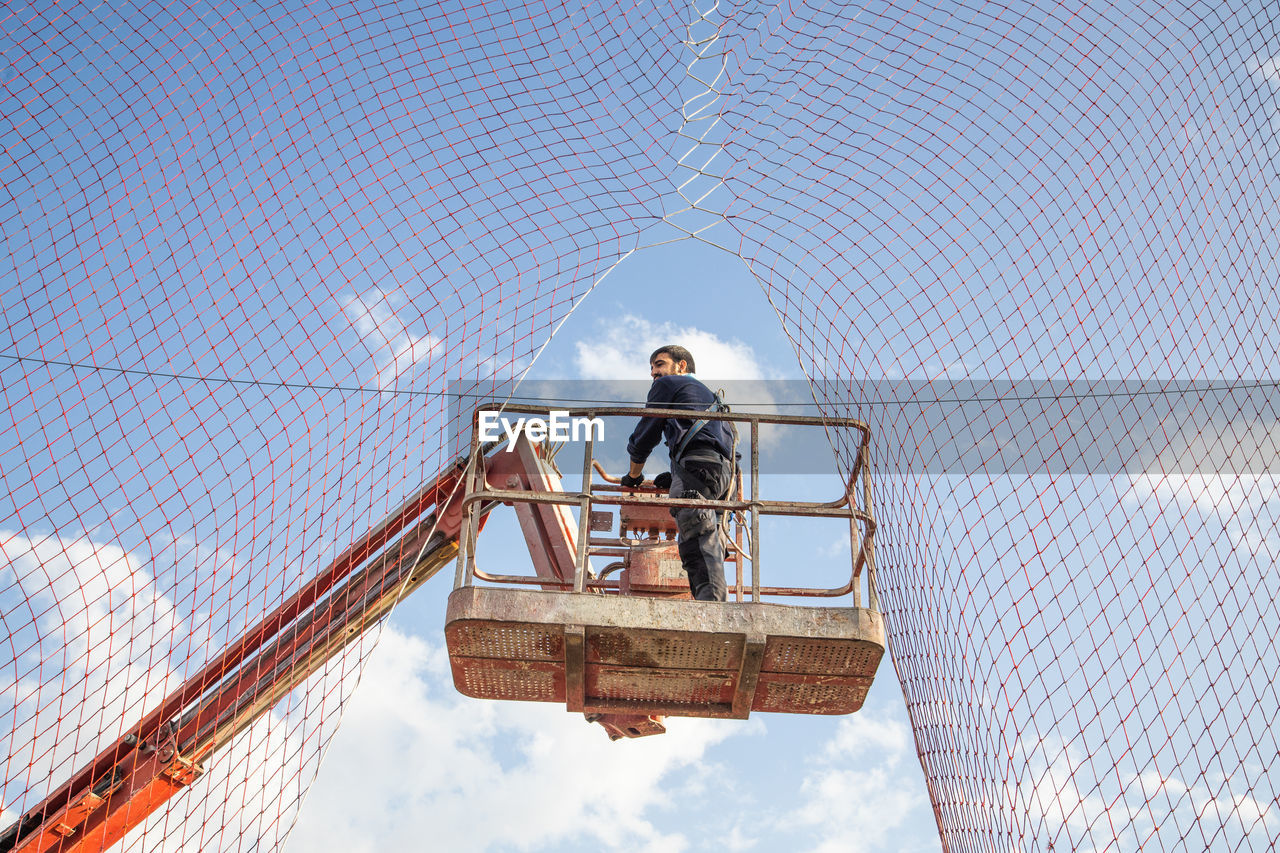 Low angle view of man working while standing on crane