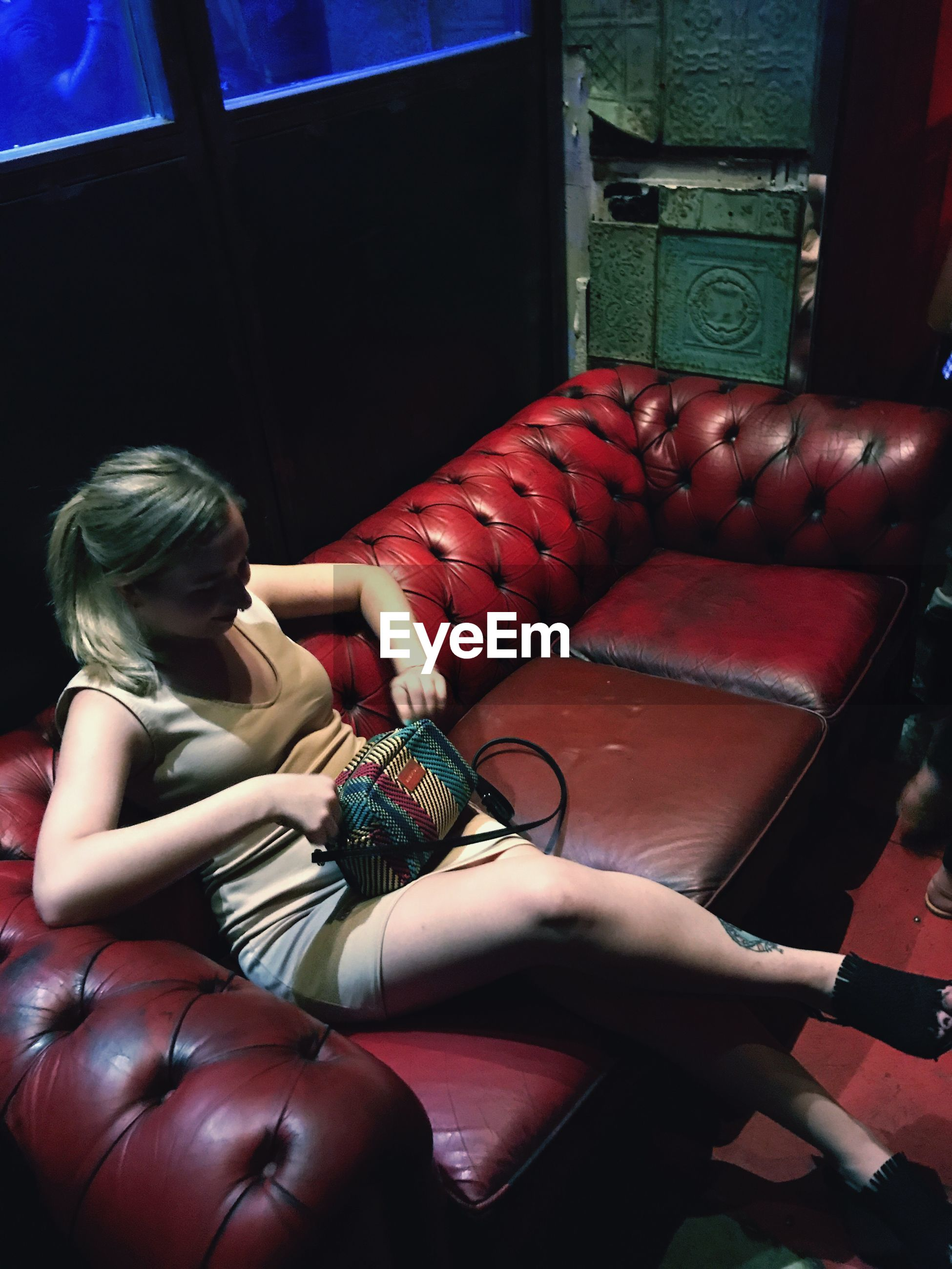 High angle view of young woman holding purse while sitting on couch at nightclub