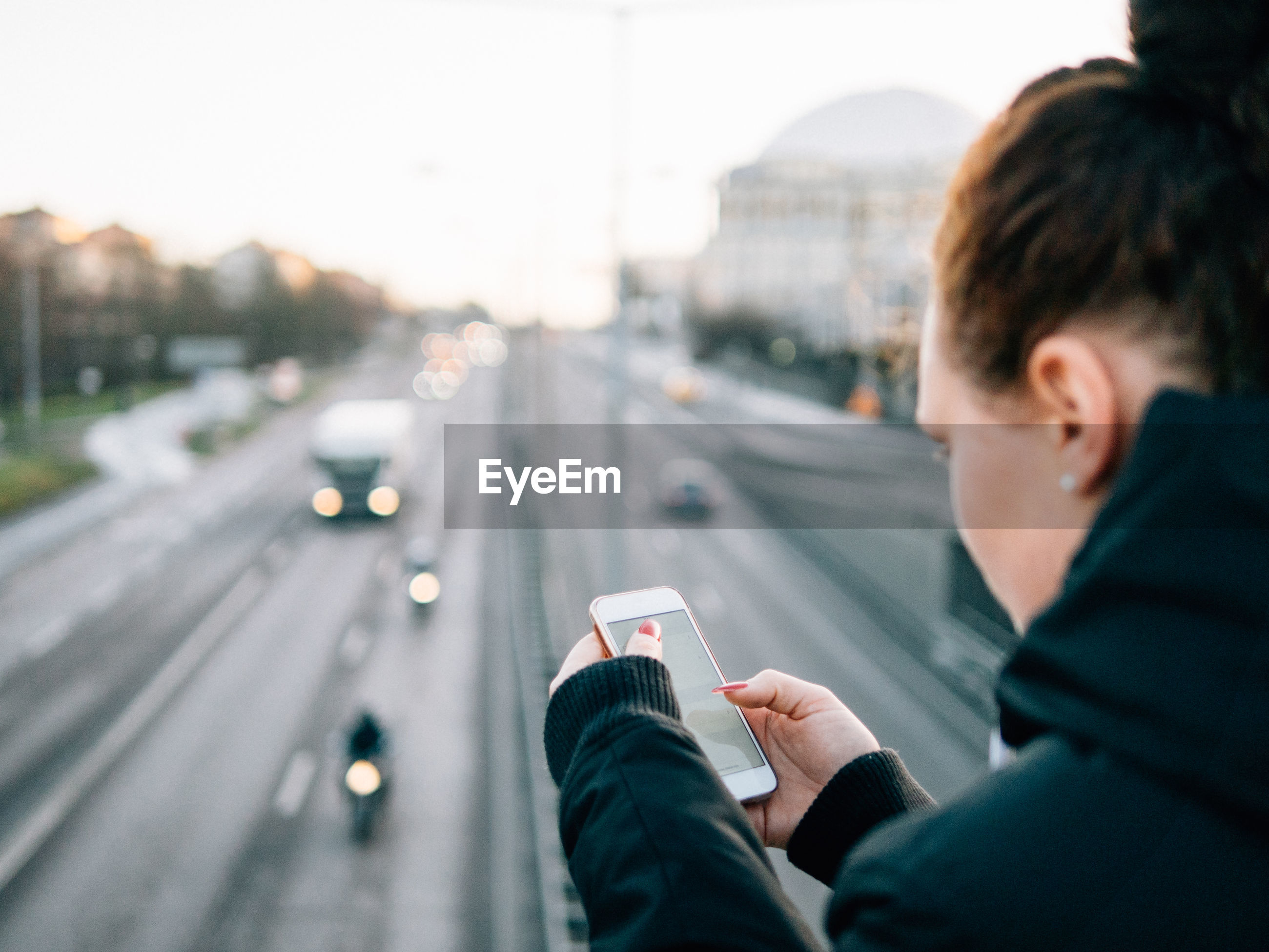 Close-up of young woman using smart phone against road in city