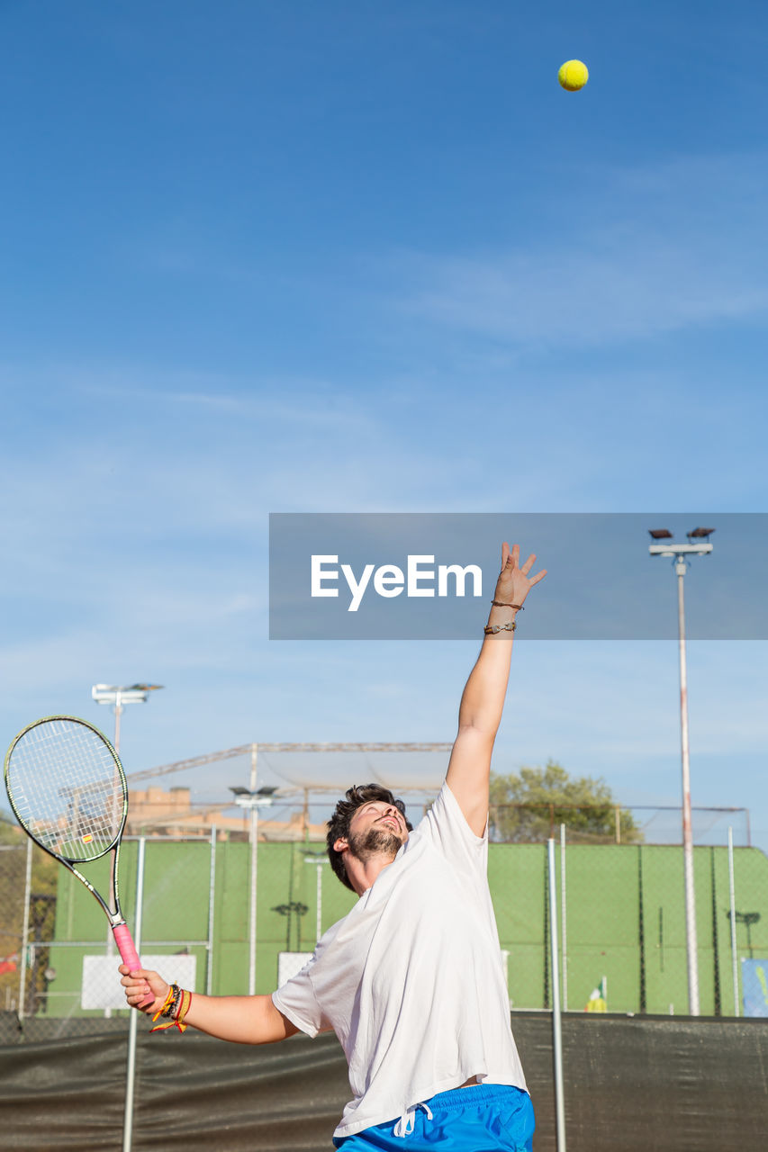 Young man playing tennis against sky