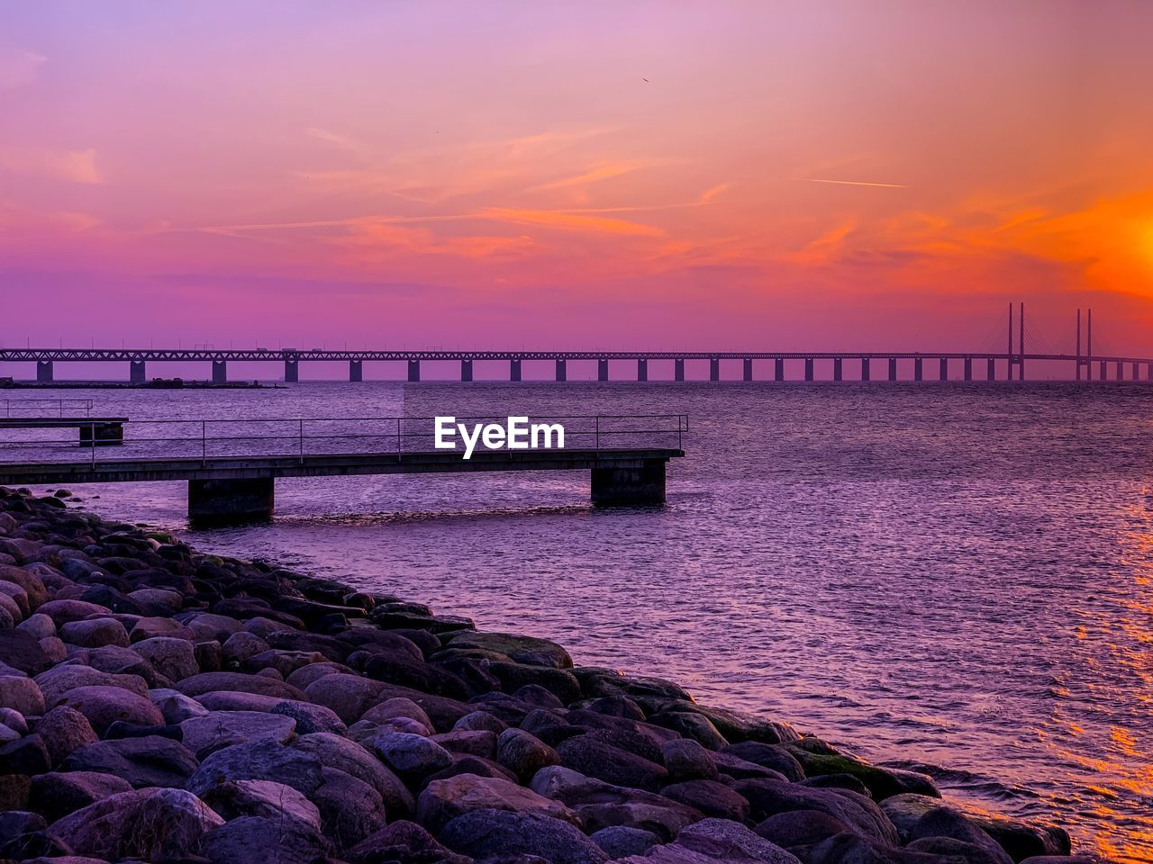 sky, sunset, water, beauty in nature, scenics - nature, sea, cloud - sky, orange color, nature, tranquil scene, tranquility, idyllic, pier, rock, built structure, bridge, no people, rock - object, solid, purple, groyne