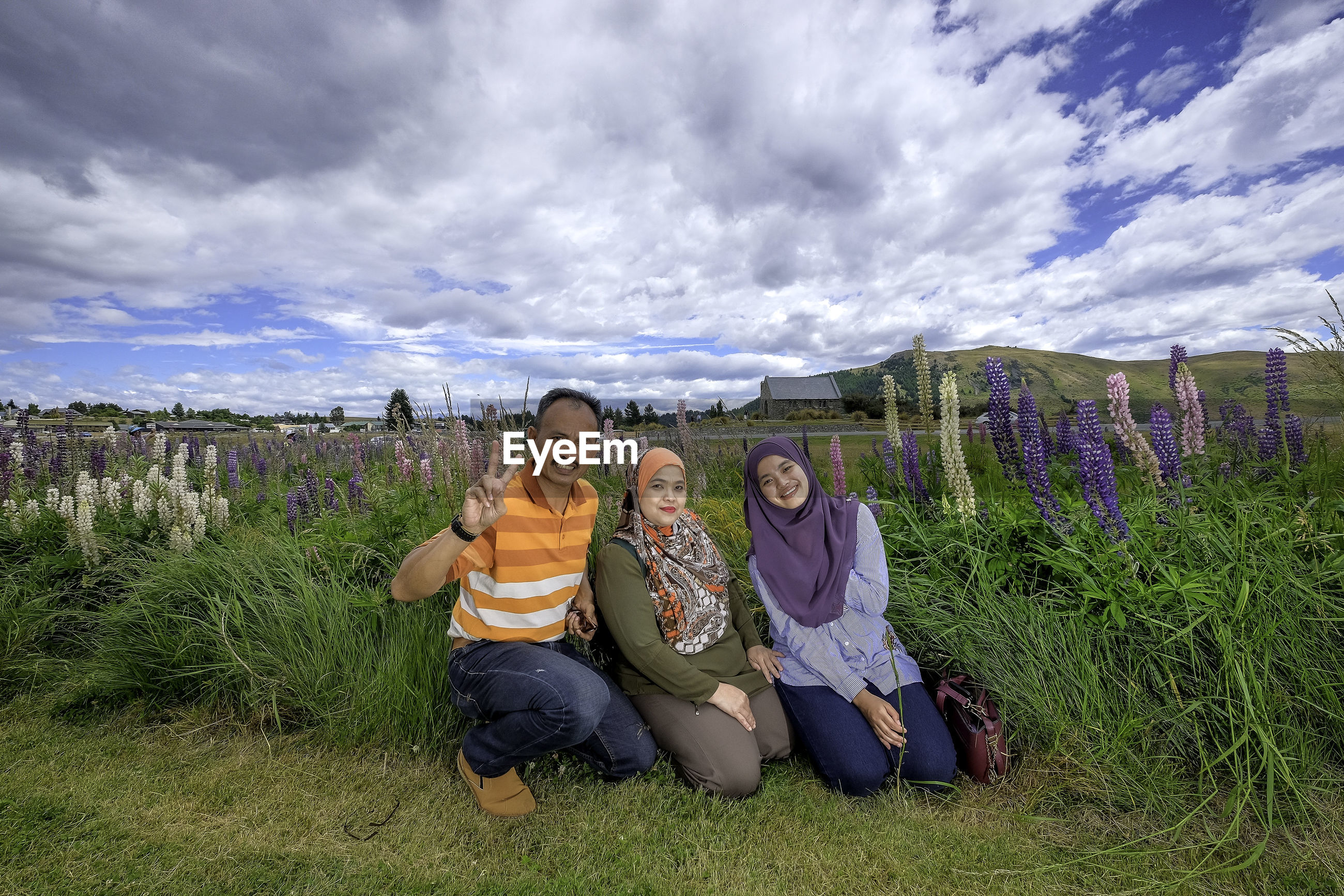 Portrait of smiling family on grassy field against cloudy sky