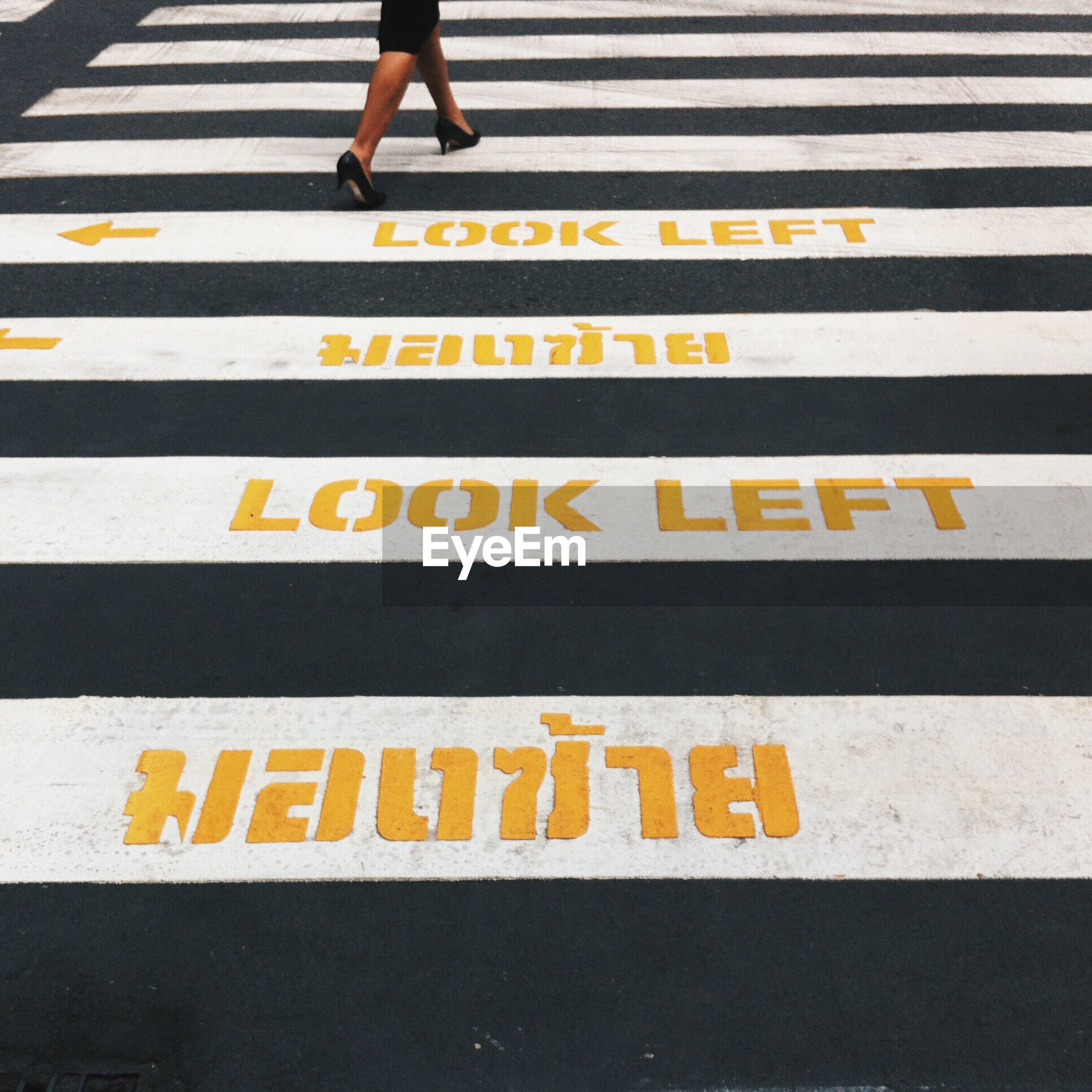 Low section of woman walking on zebra crossing road sign