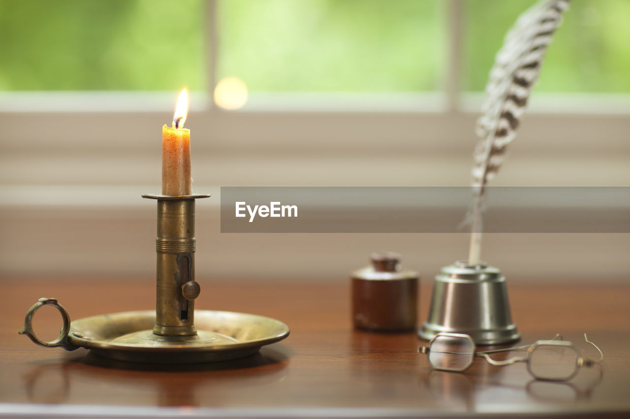 Old lit candle with quill pen and eyeglasses on table