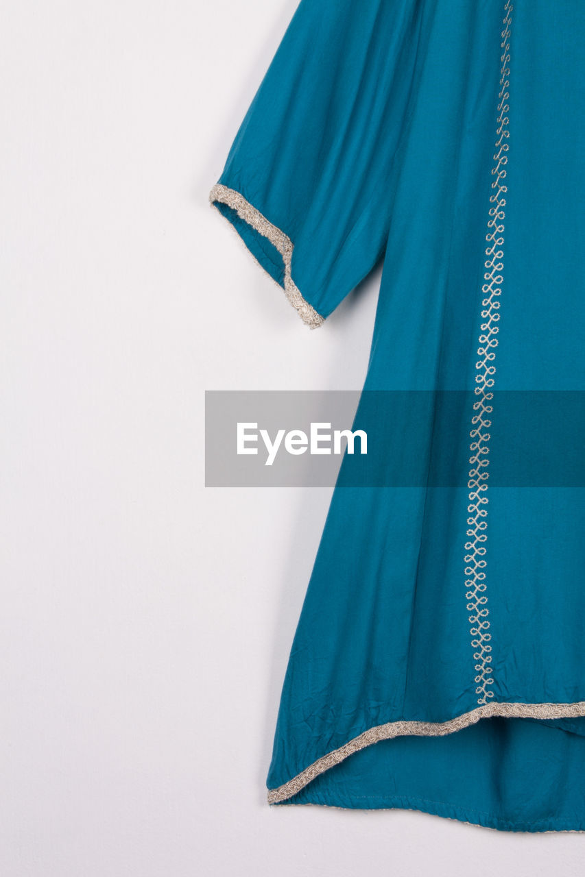 Close-up of blue dress against white background