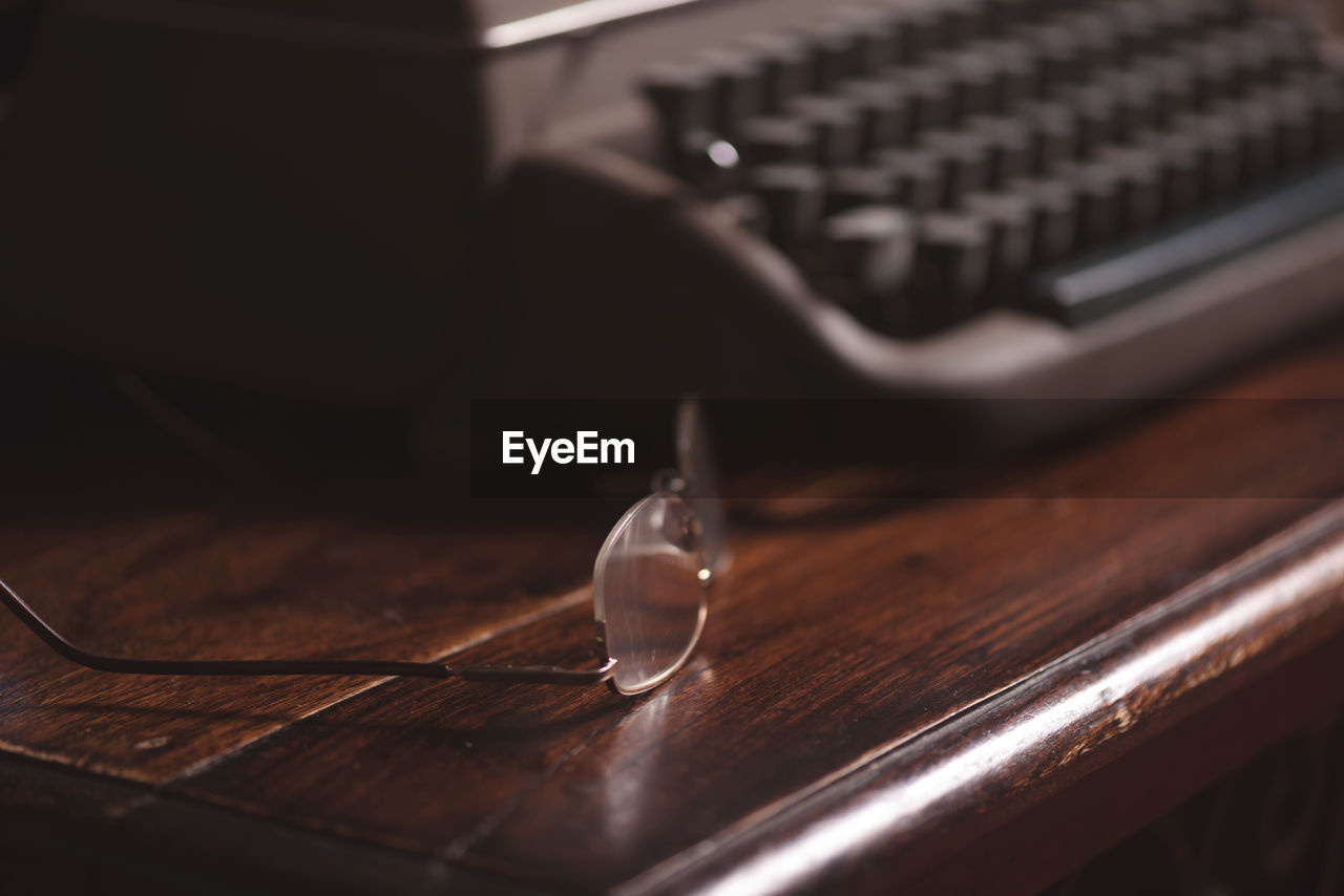Close-Up Of Eyeglasses By Typewriter On Table