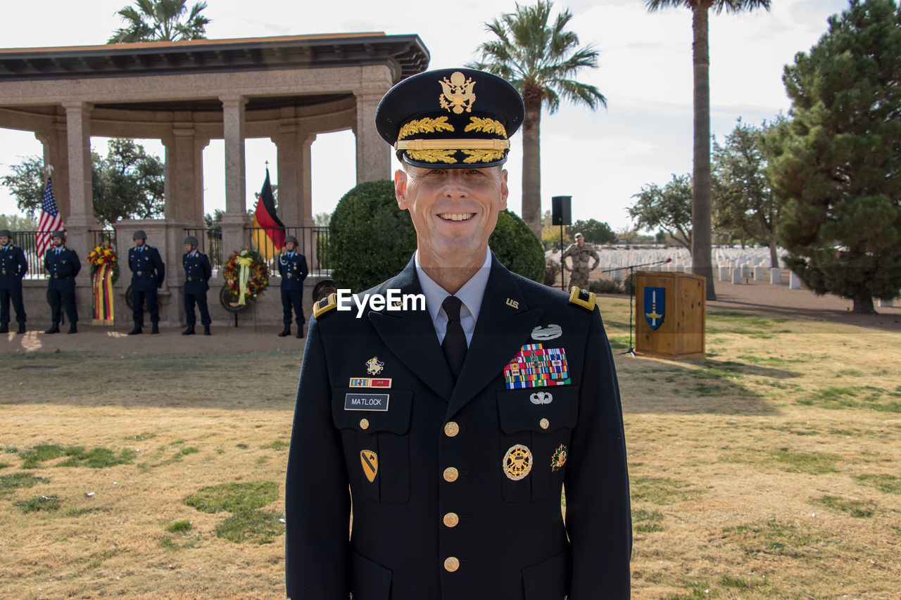 portrait, looking at camera, standing, front view, one person, uniform, clothing, day, men, real people, government, incidental people, pride, adult, outdoors, military, focus on foreground, architecture, plant, officer