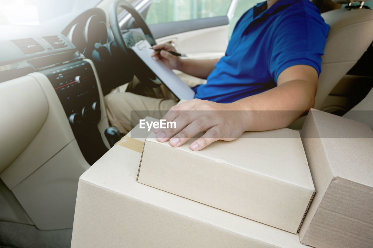 Midsection of delivery person sitting in car