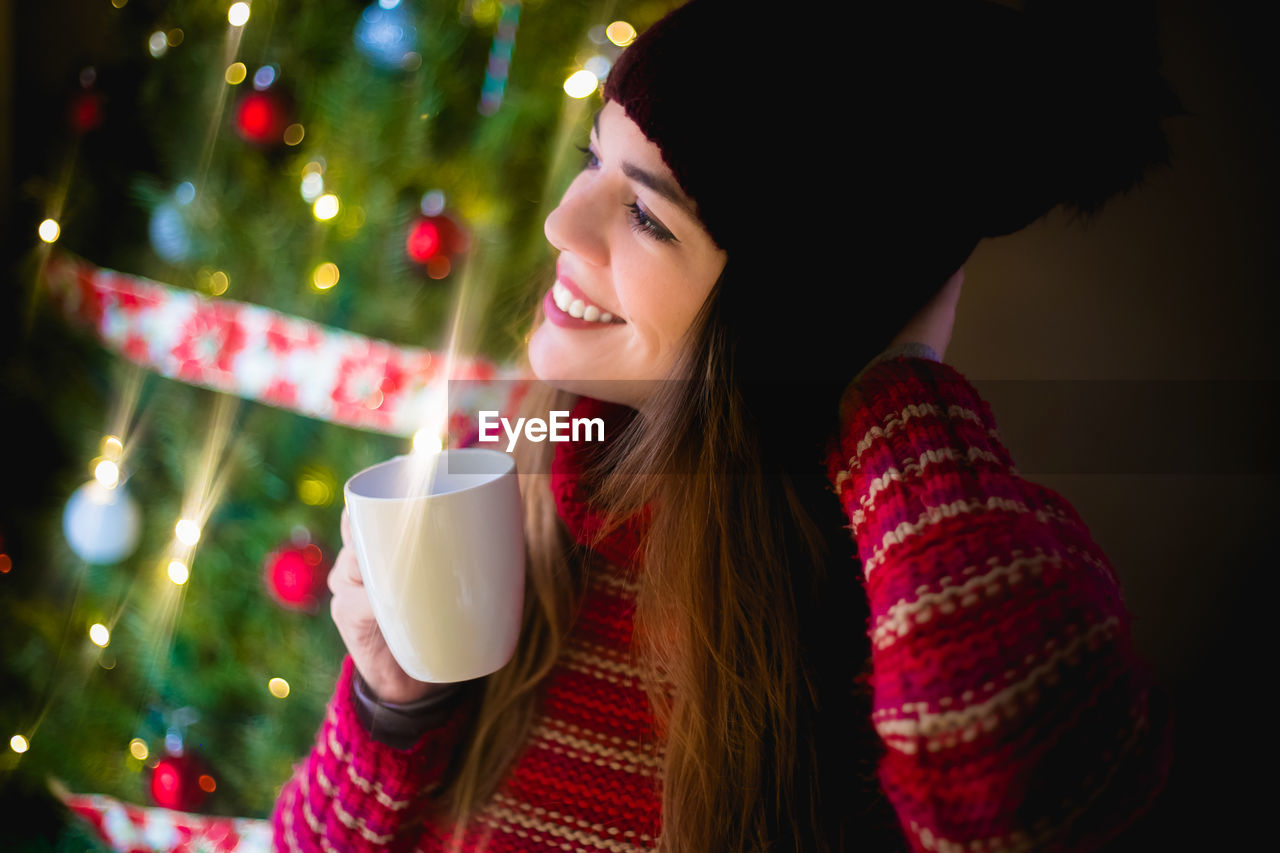 MIDSECTION OF WOMAN DRINKING COFFEE AT CHRISTMAS