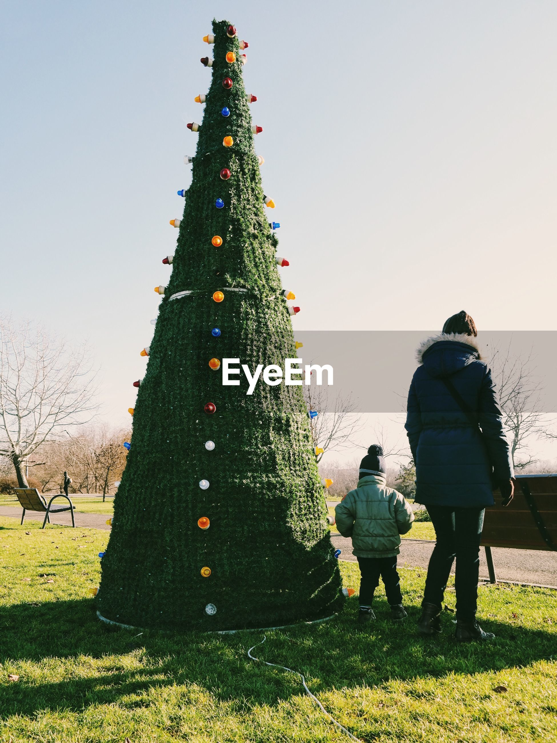 Family standing by christmas tree against clear sky