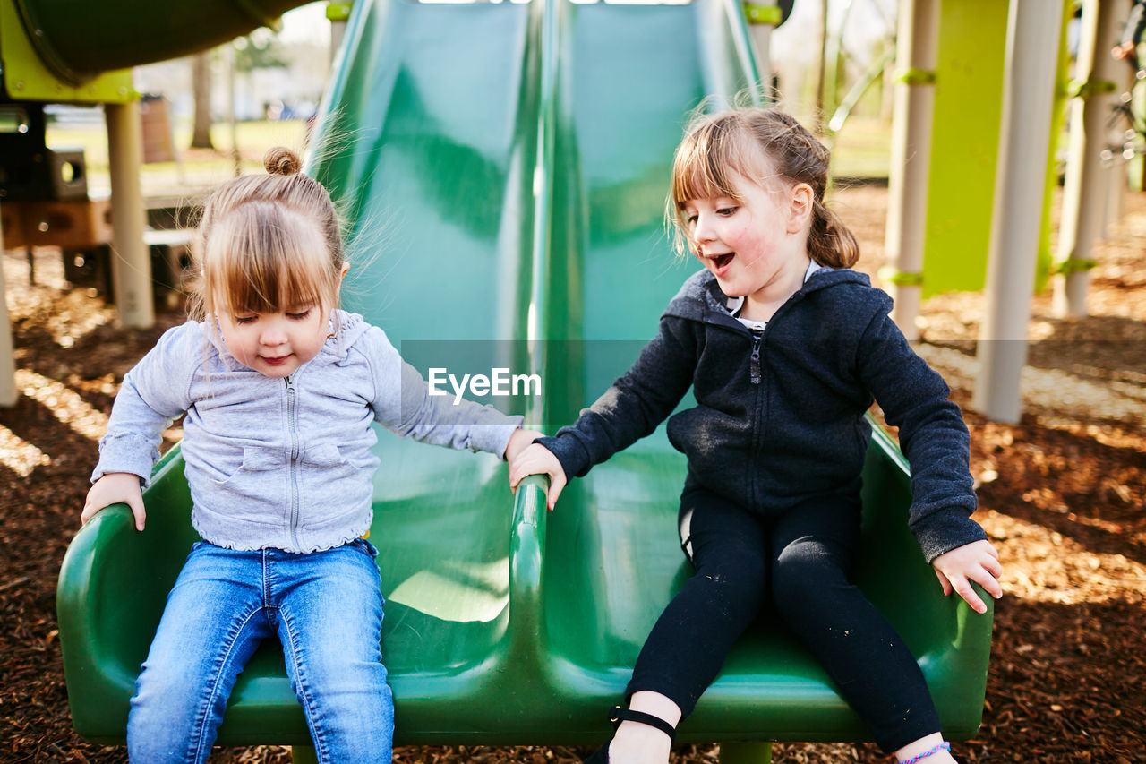 child, childhood, two people, family, togetherness, women, happiness, girls, females, emotion, real people, casual clothing, smiling, three quarter length, boys, playground, innocence, positive emotion, daughter, sister