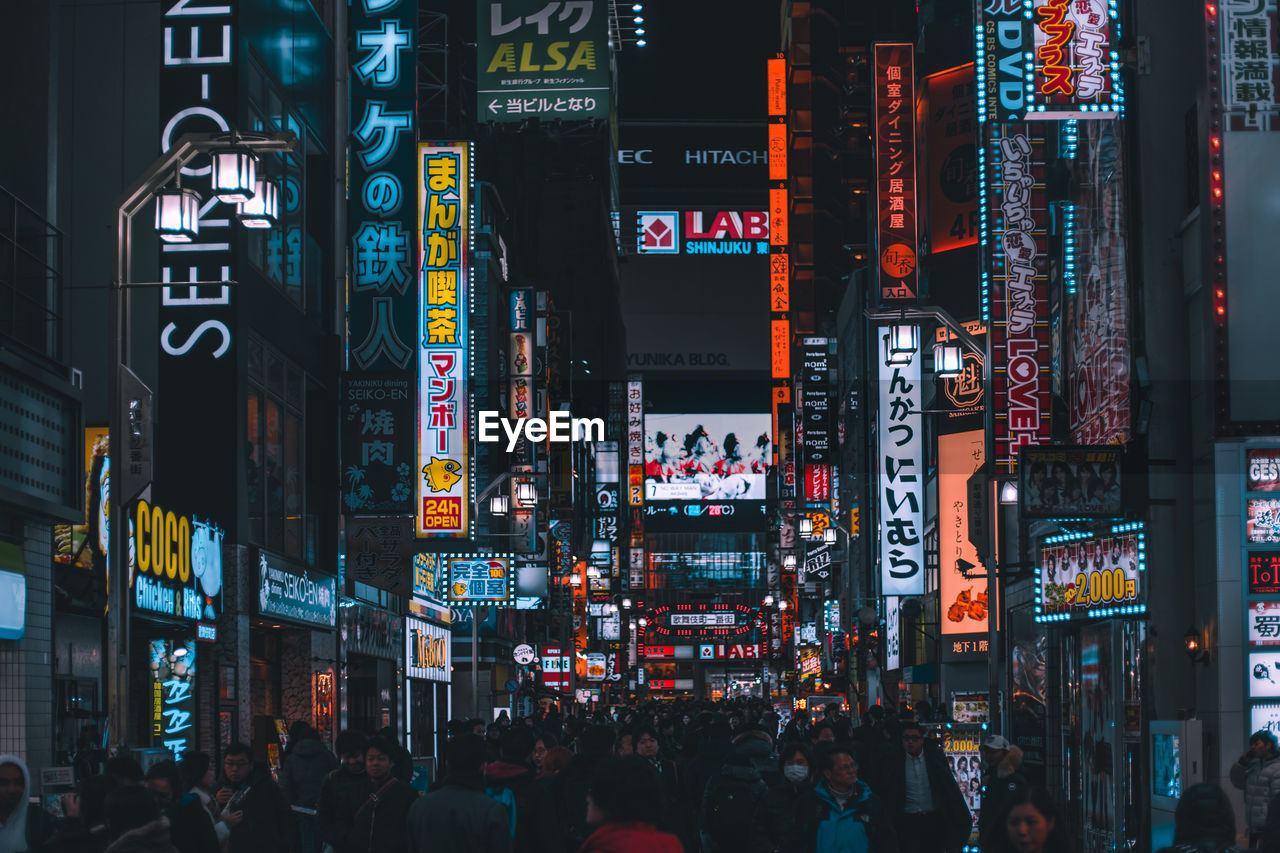 illuminated, city, building exterior, architecture, built structure, text, communication, advertisement, night, street, city life, group of people, neon, crowd, commercial sign, sign, large group of people, real people, script, non-western script, city street, outdoors, nightlife, office building exterior, skyscraper