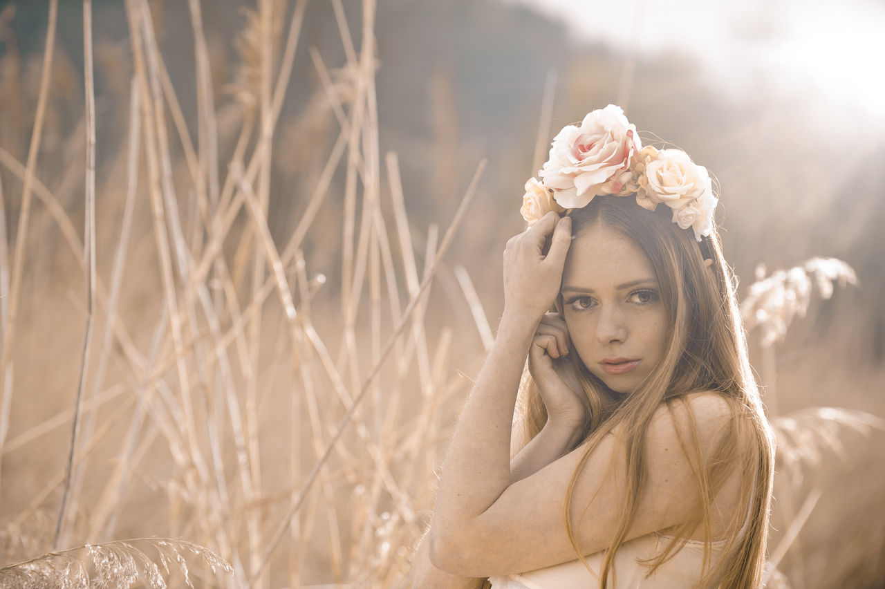portrait, young adult, one person, looking at camera, beautiful woman, beauty, young women, plant, women, leisure activity, long hair, hairstyle, front view, focus on foreground, nature, headshot, real people, lifestyles, hair, outdoors, contemplation, teenager