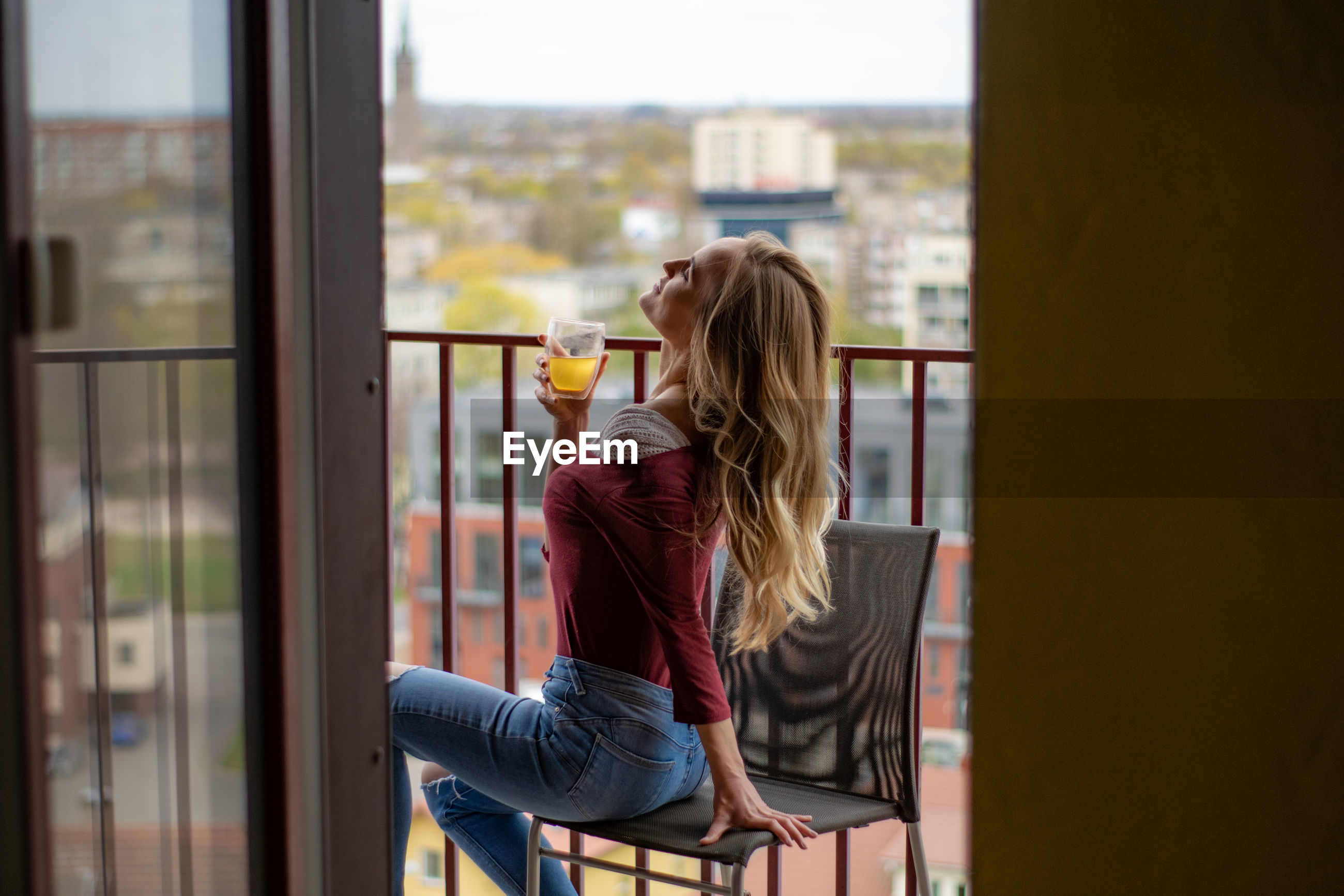 Side view of woman having drink while sitting on chair