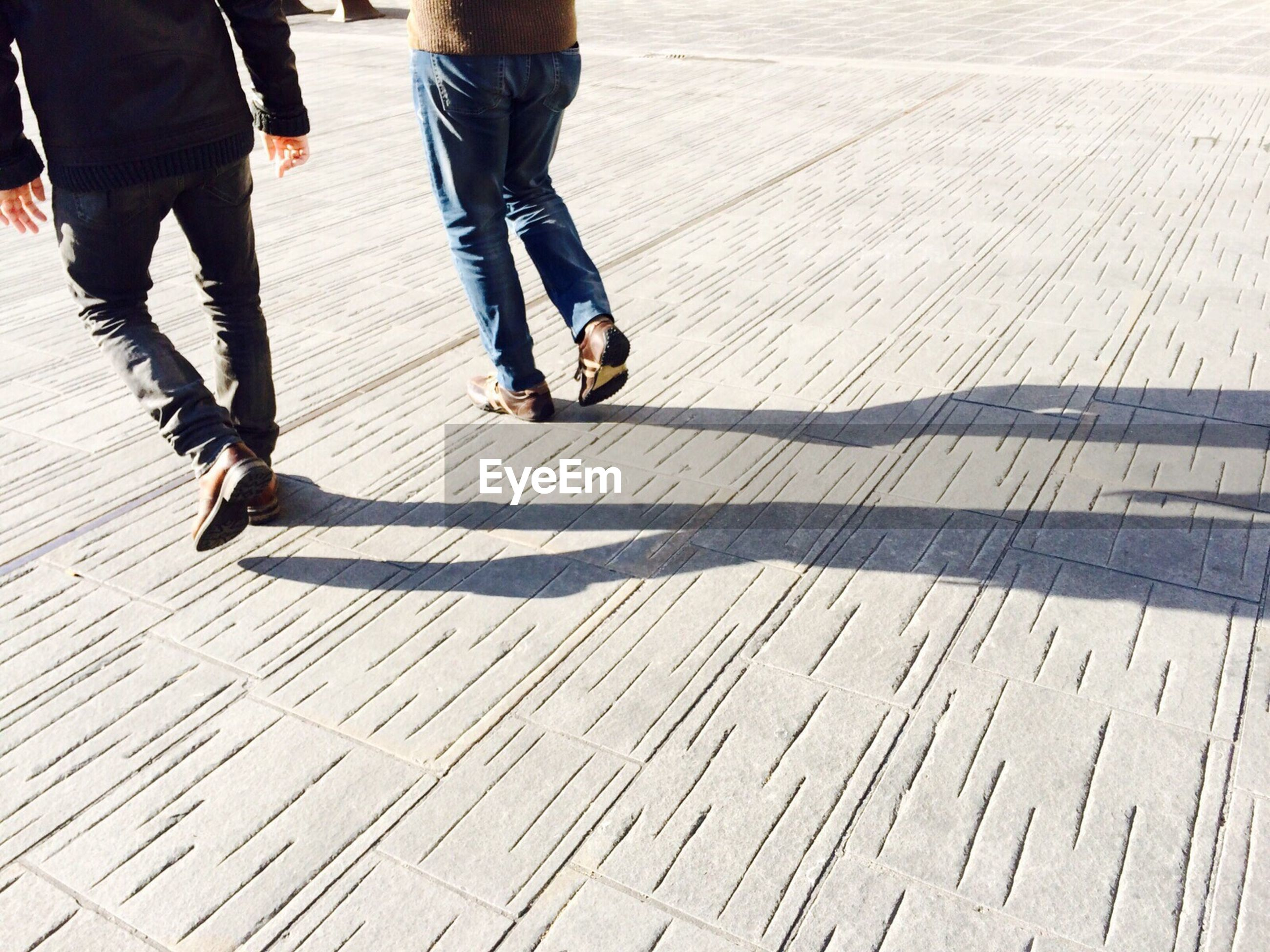 low section, shadow, person, sunlight, walking, motion, lifestyles, day, outdoors