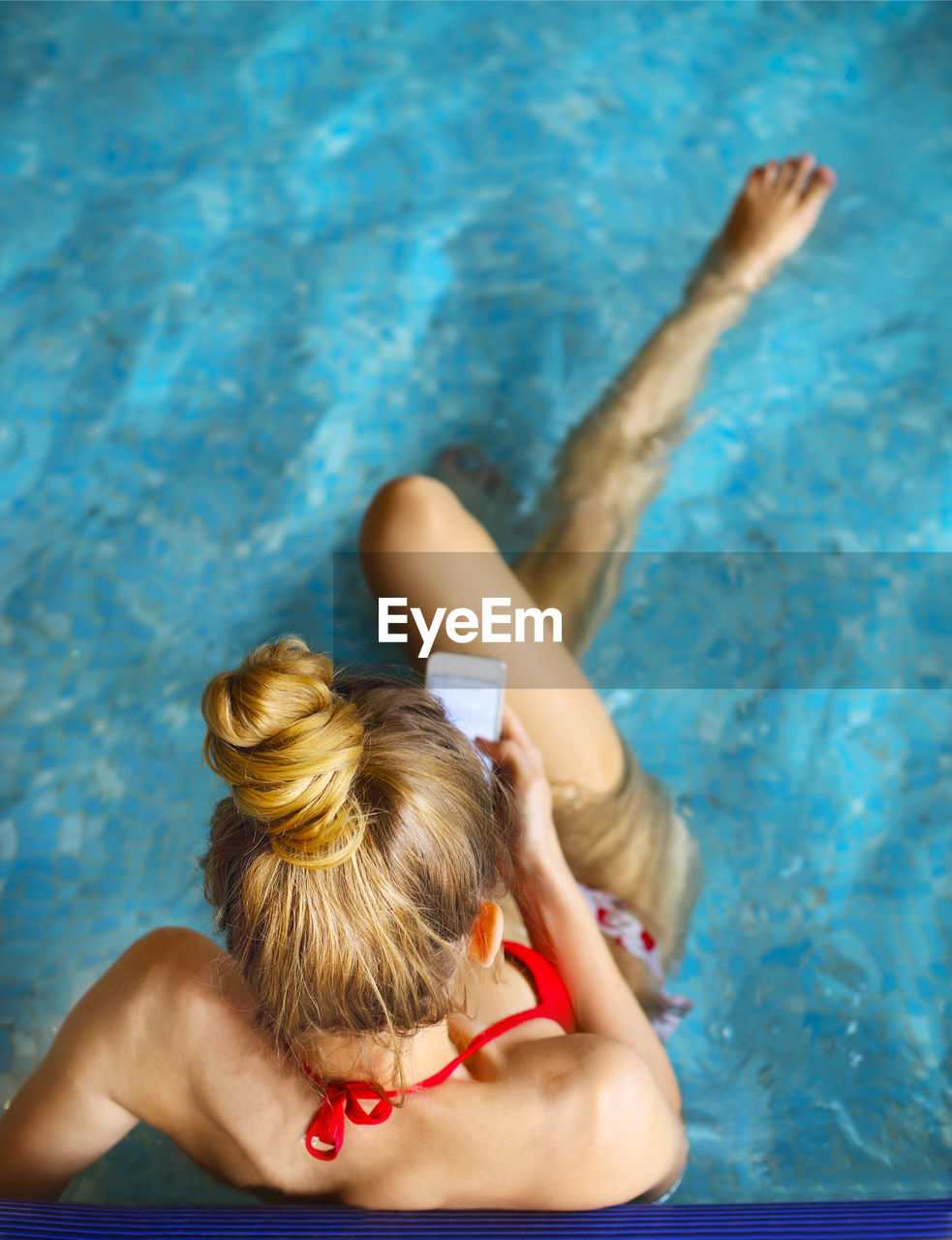 HIGH ANGLE VIEW OF WOMAN HOLDING SWIMMING POOL