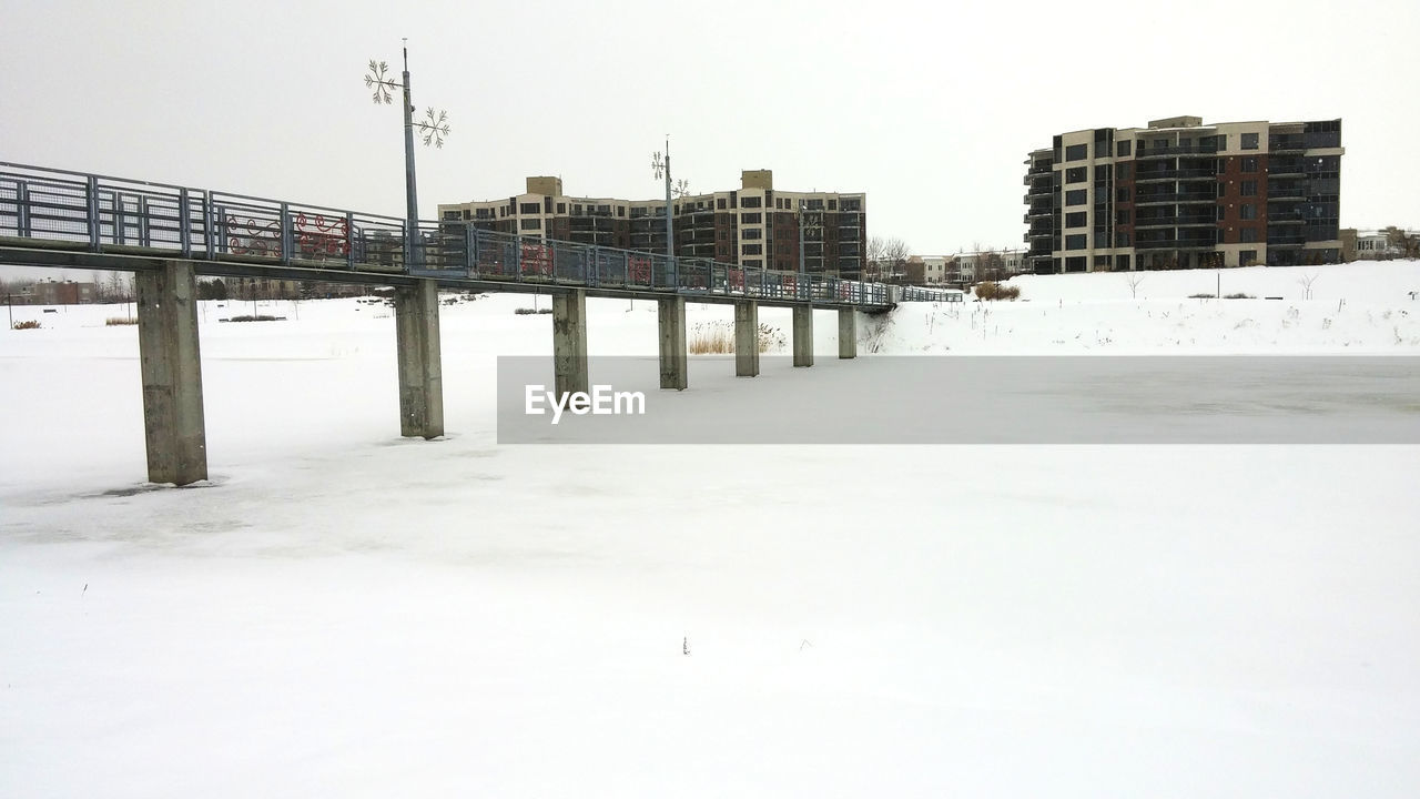 Bridge over frozen river against clear sky in city