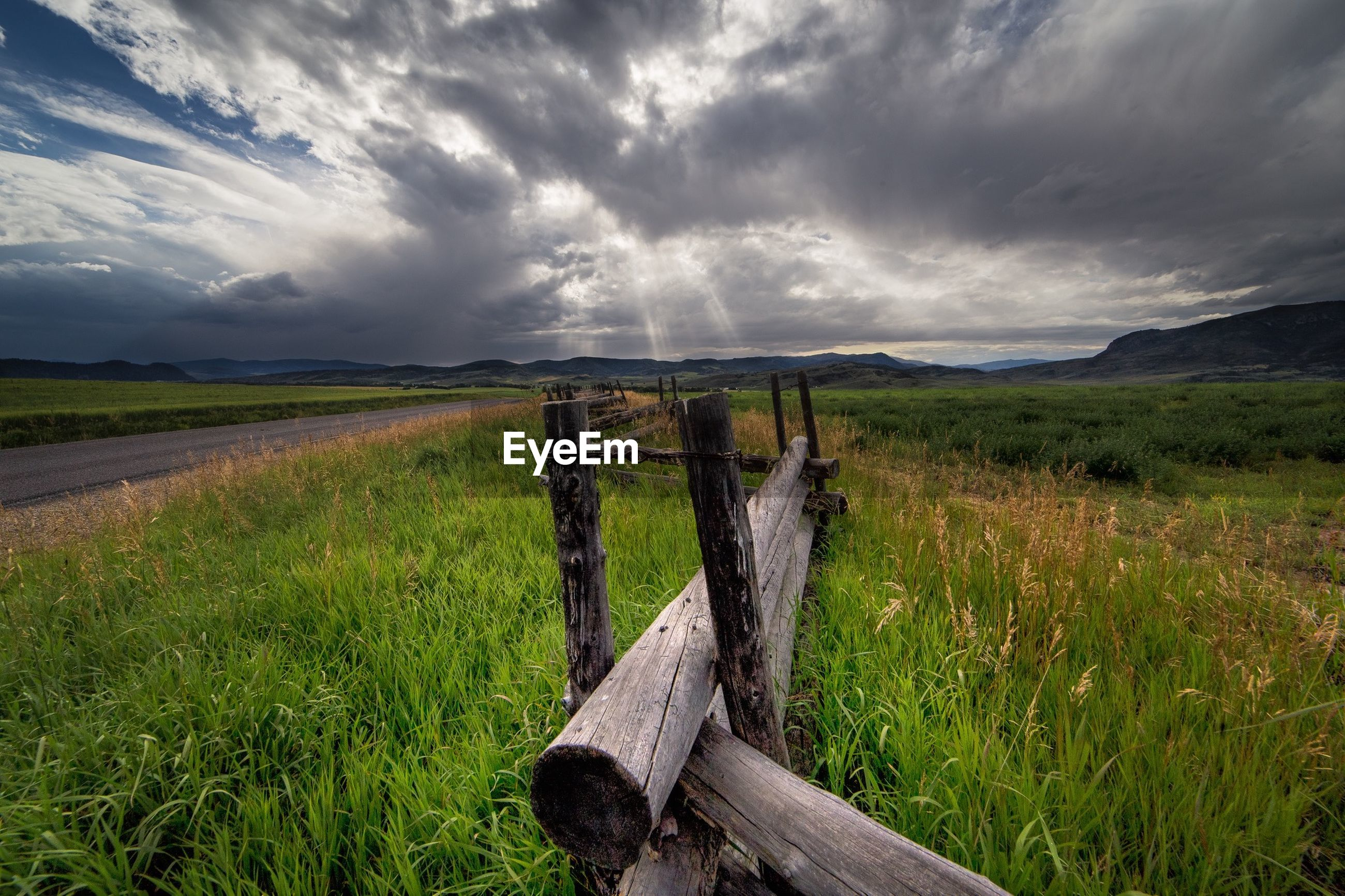 Wooden fence on field against cloudy sky