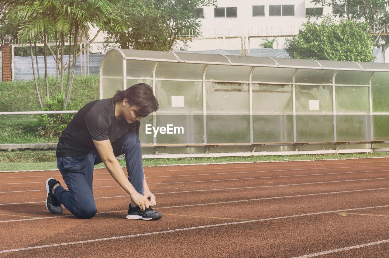Man tying shoelace on running track