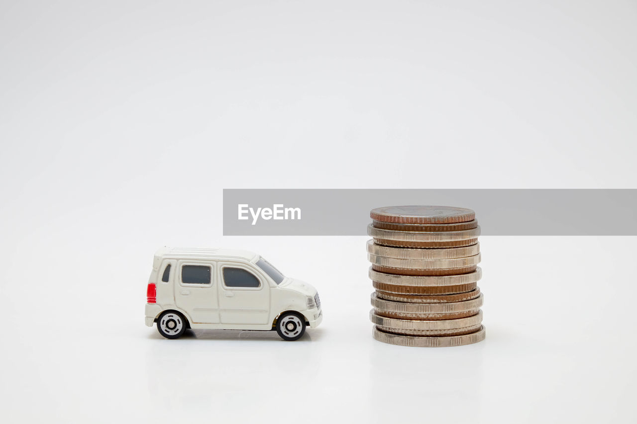 Close-up of toy car by coins against white background